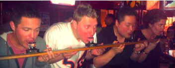 Blackhawks fans pause to share a shot ski at Lottie's Pub.