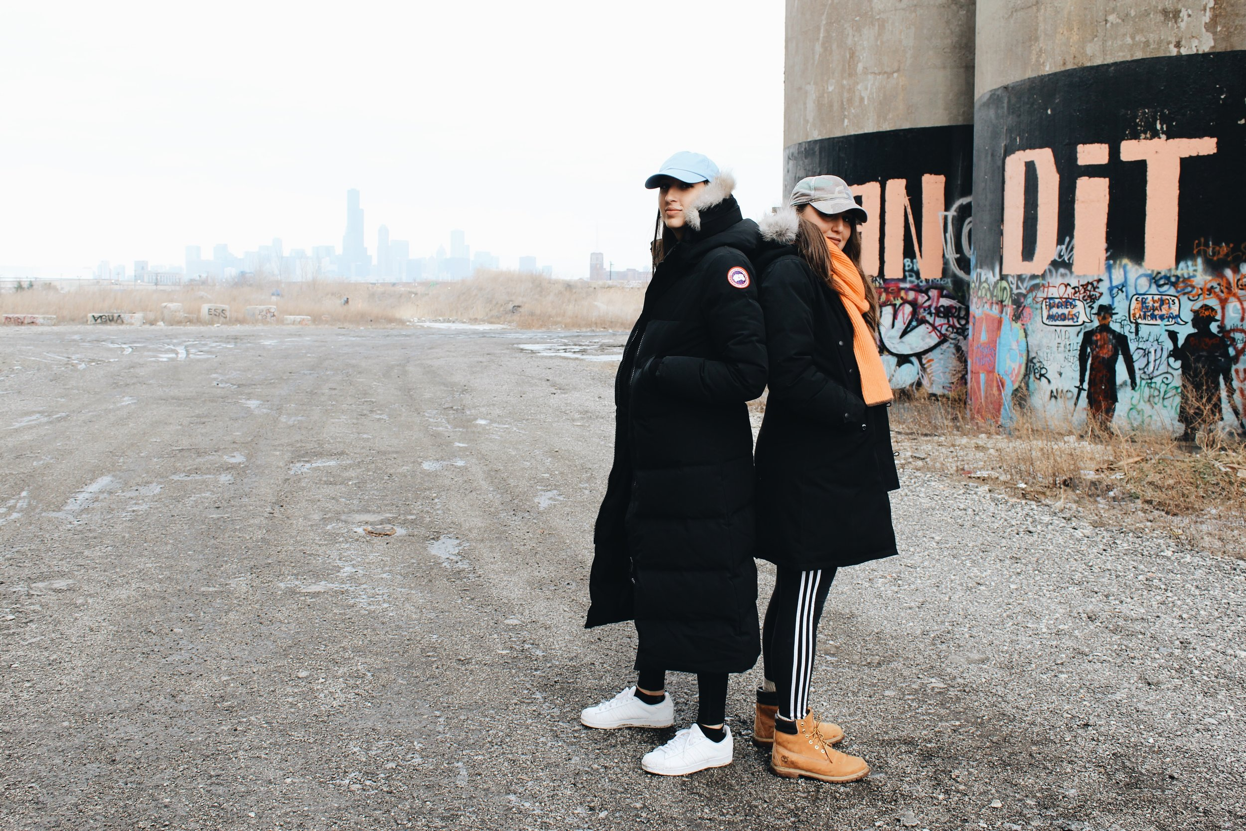 Amanda wears hat, Anti Social Social Club; coat, Canada Goose; leggings, Girlfriend Collective; sneakers, Adidas. Naomi wears hat, Topshop; scarf, Hermès; coat, Canada Goose; leggings, Adidas; boots, Timberland.