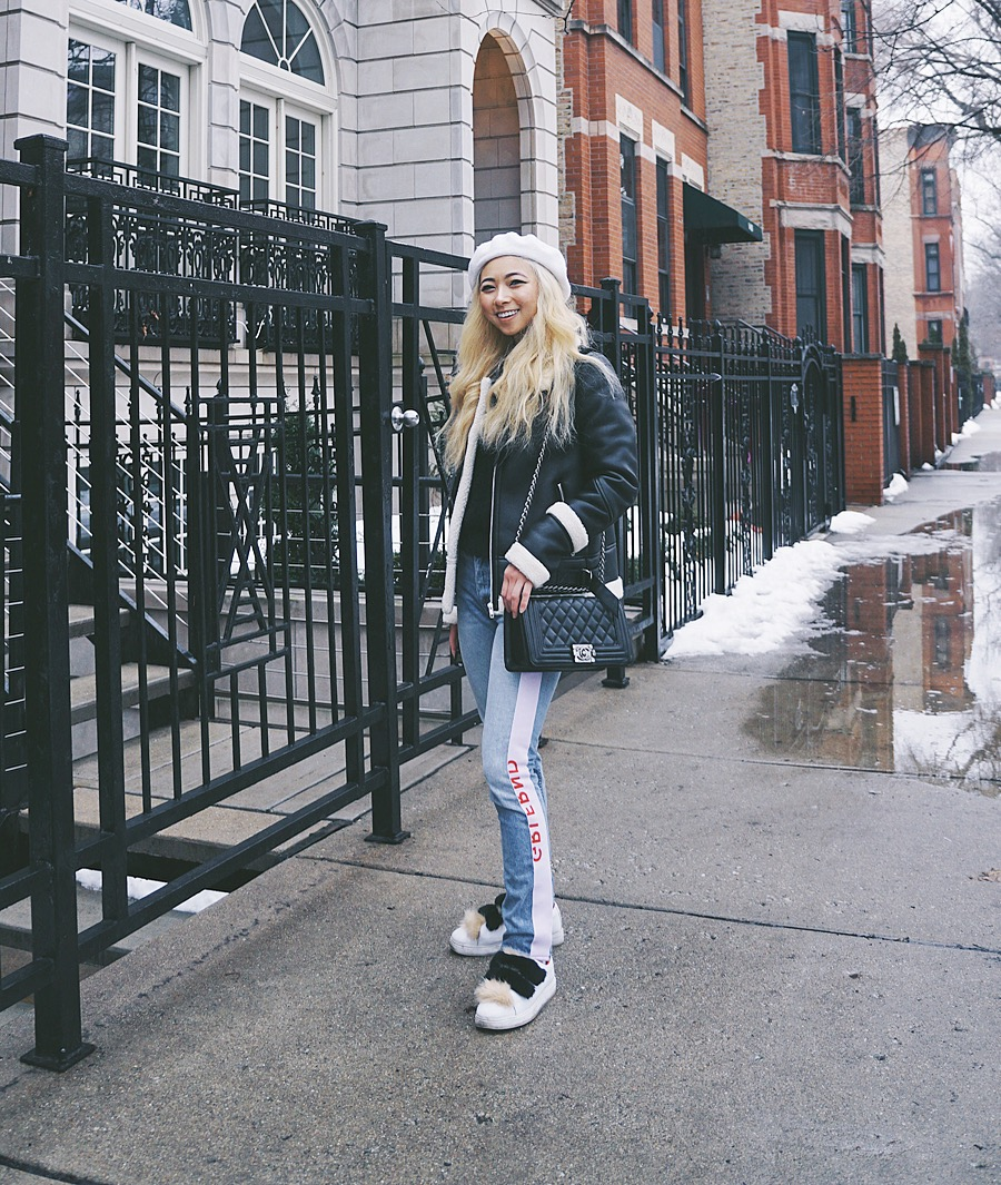 Ginger wears beret hat,  Topshop ; Piper Moto Jacket,  EAVES ; fuzzy black sweater,  Forever 21 ; Boy Bag,  Chanel ; jeans, GRLFRND; sneakers,  Zara .