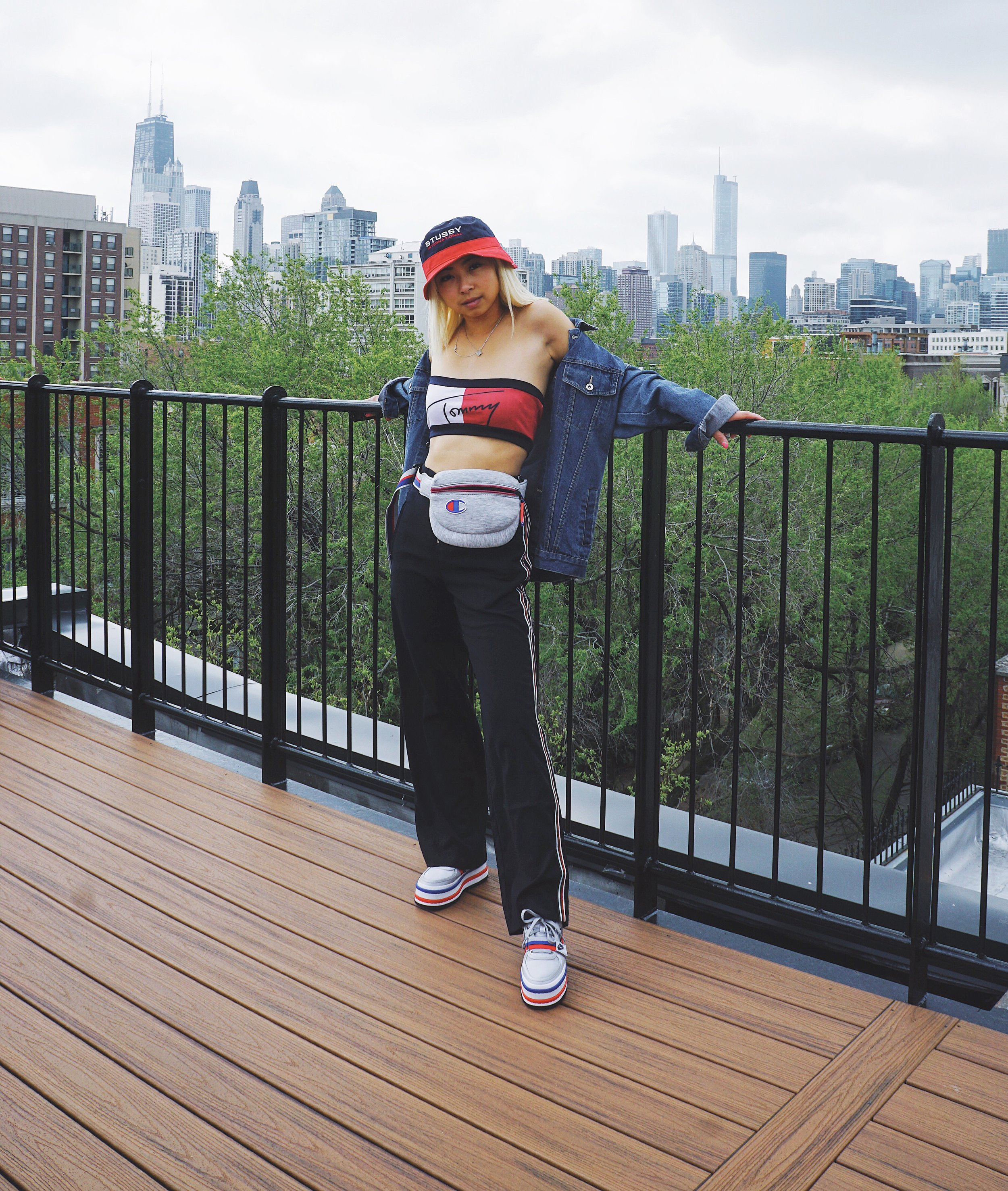 Ginger wears bucket hat,  Stussy ; Tommy bandeau,  Etsy ; denim jacket,  Tommy Hilfiger ; waist bag,  Champion ; Zoe Pants,  Publish Brand ; Nike Vandal 2K;  Nike .
