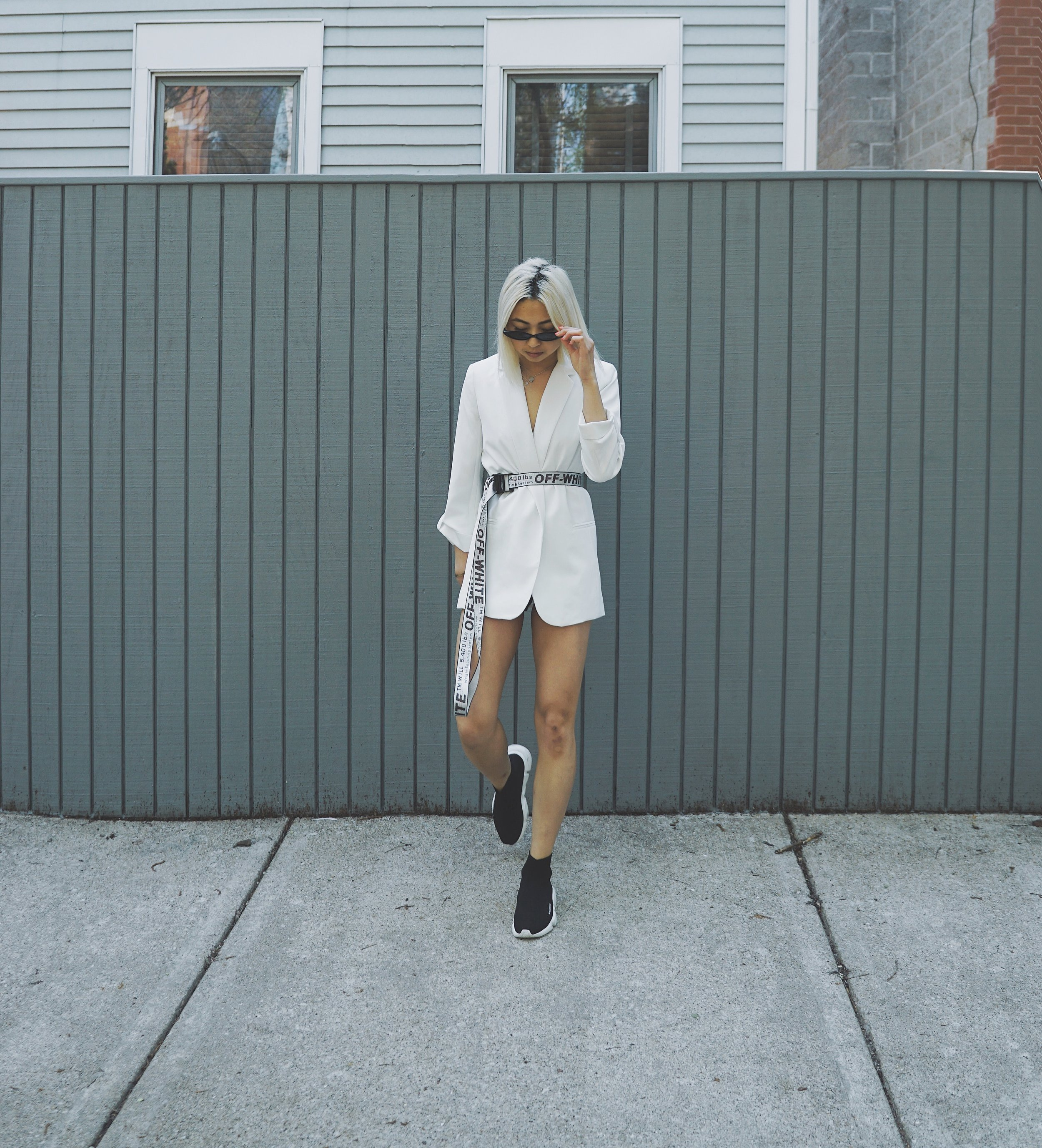 Ginger wears white blazer,  YSL ; belt,  Off-White ;  Sock Sneakers , Balenciaga.