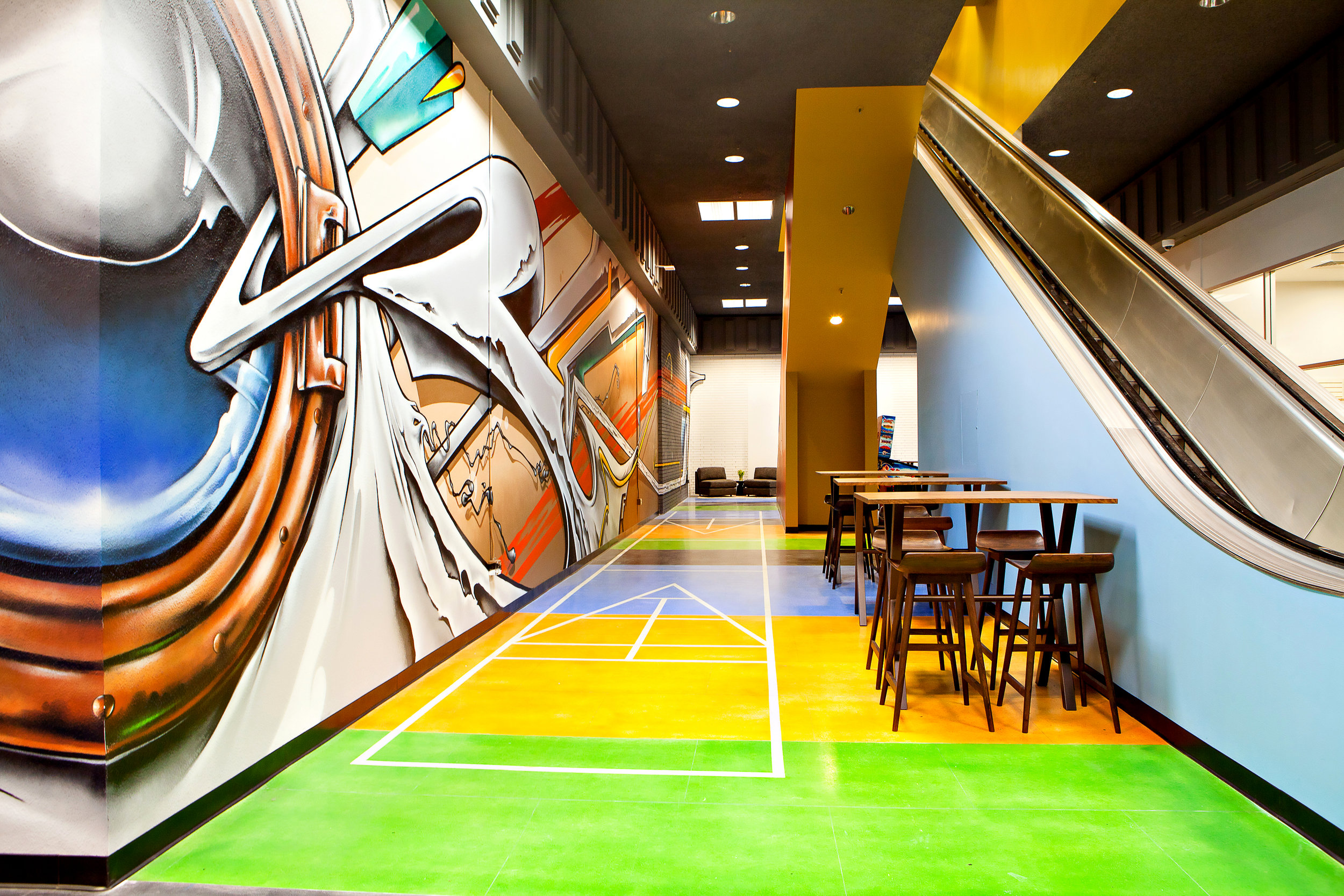 On the first floor, the open co-working space is filled with the articulated 'IceBerg' seating, stripped floors and a dramatic, full wall graffiti mural.