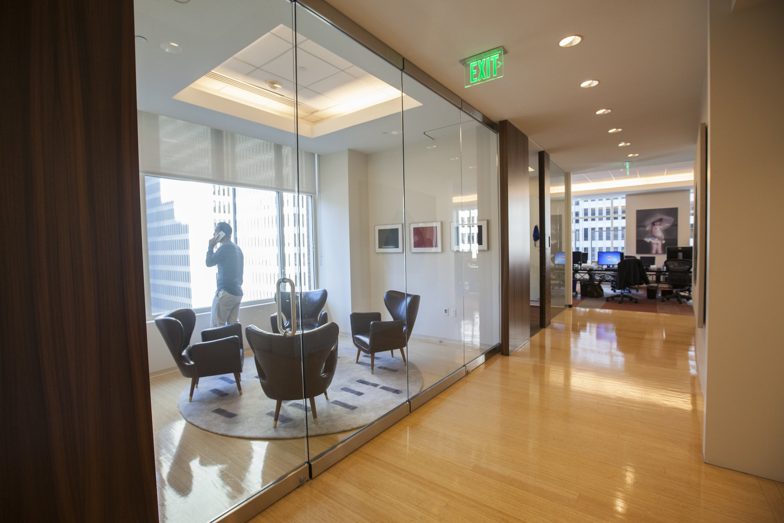 As you round the corner of the elevator lobby, the hall leads you to a private meeting space flanked by offices and conference rooms. Now with this operational glass wall it has the ability to be fully closed off with a door, or a fully open space.