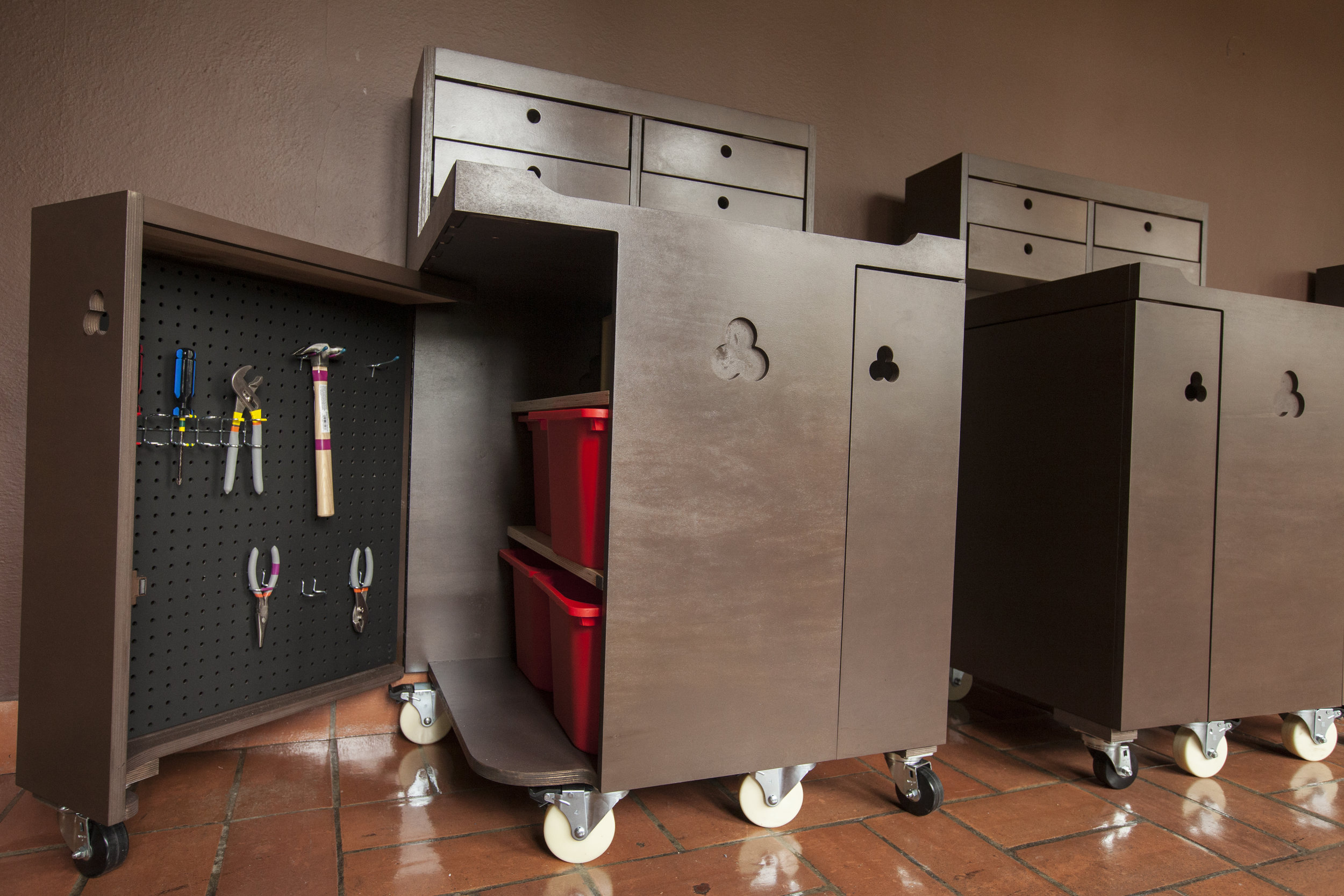 The doors open completely to allow access to the pegboard of tools, the white board for notes, and the central cavity with ample storage for projects and parts.