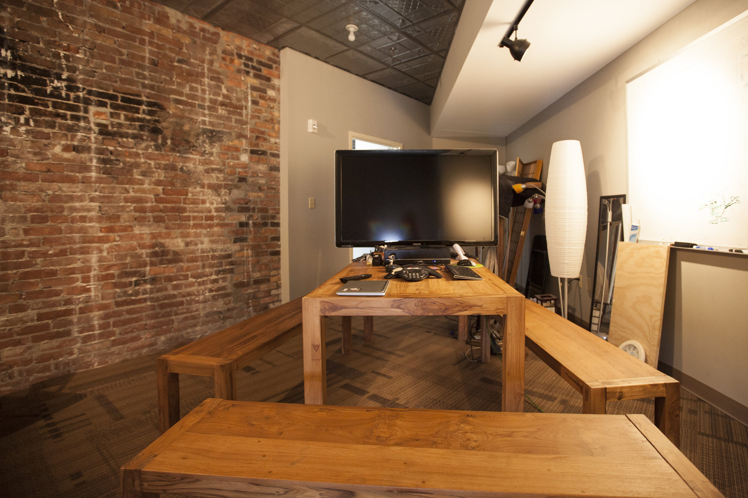 Other small and difficult spaces needed quick and affordable make overs to become meeting spaces. This room has the original brick wall exposed and hardwood furniture installed.