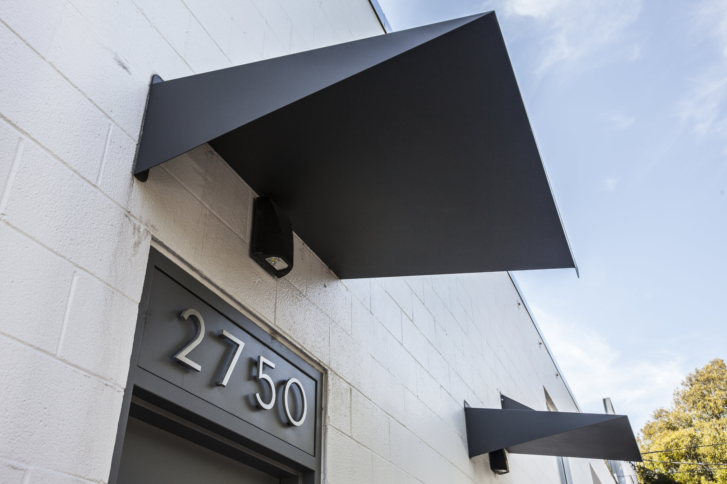 Clean discrete numbers over the doors and with custom bent steel awnings. These subtle details are discrete as this is a private building.