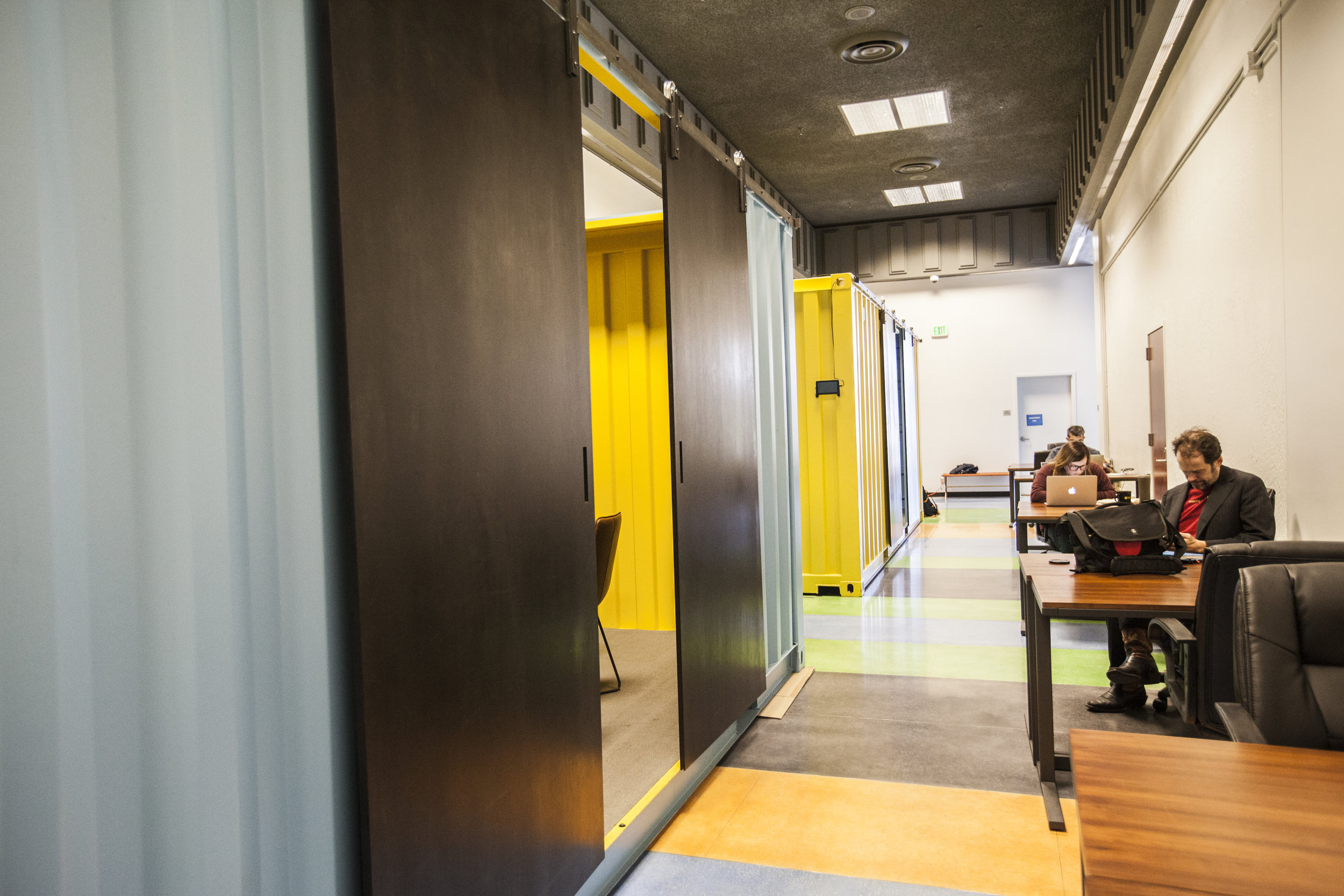 Brightly colored shipping container conference rooms with sliding doors now fill the large hallway.
