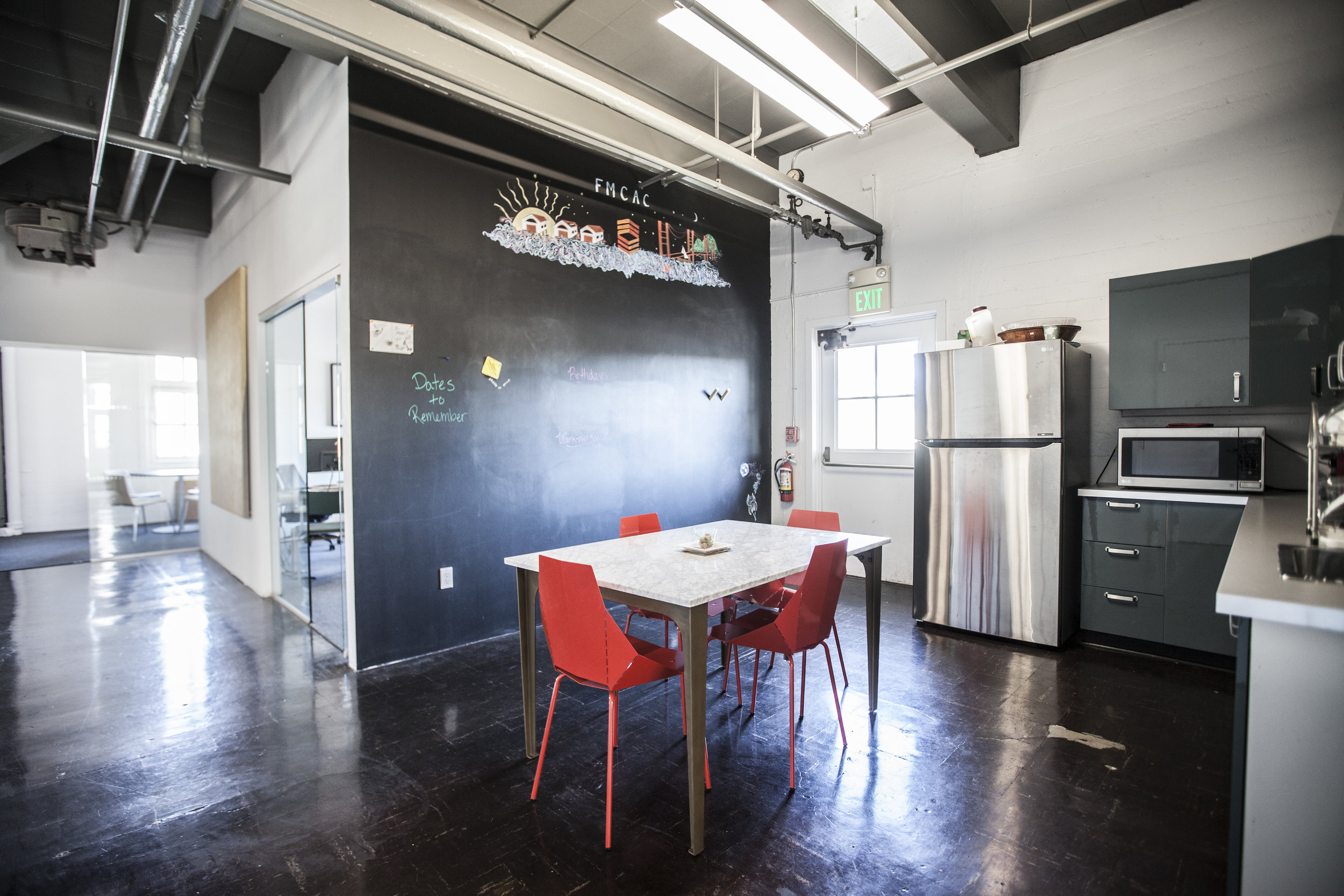 Touches of modern fun and brightness added to the kitchen area with a floor to ceiling chalk board.