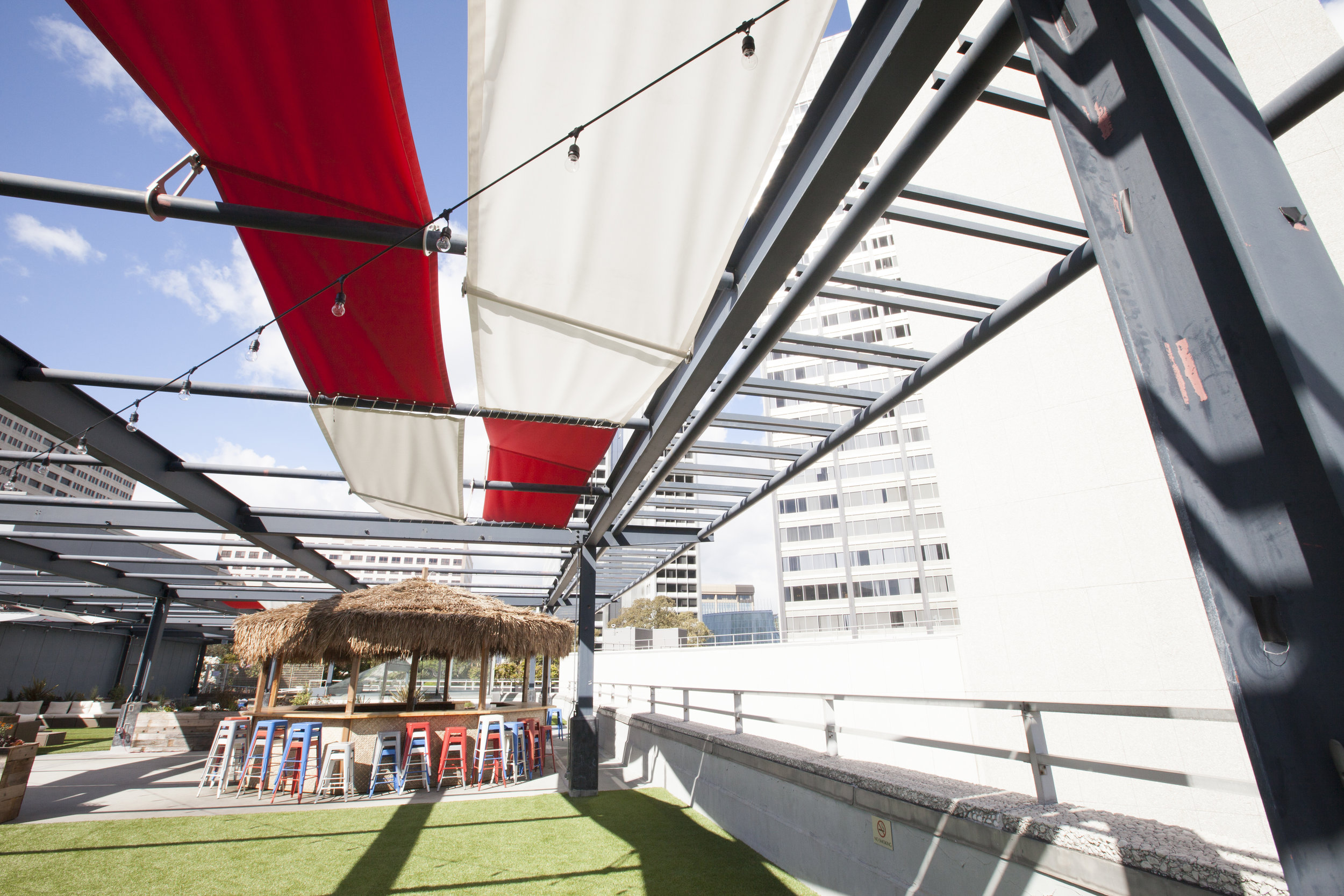 We designed an awning hanging system in red and white. The brackets add angles to the awnings allowing for different sun/shade options and visual interest.