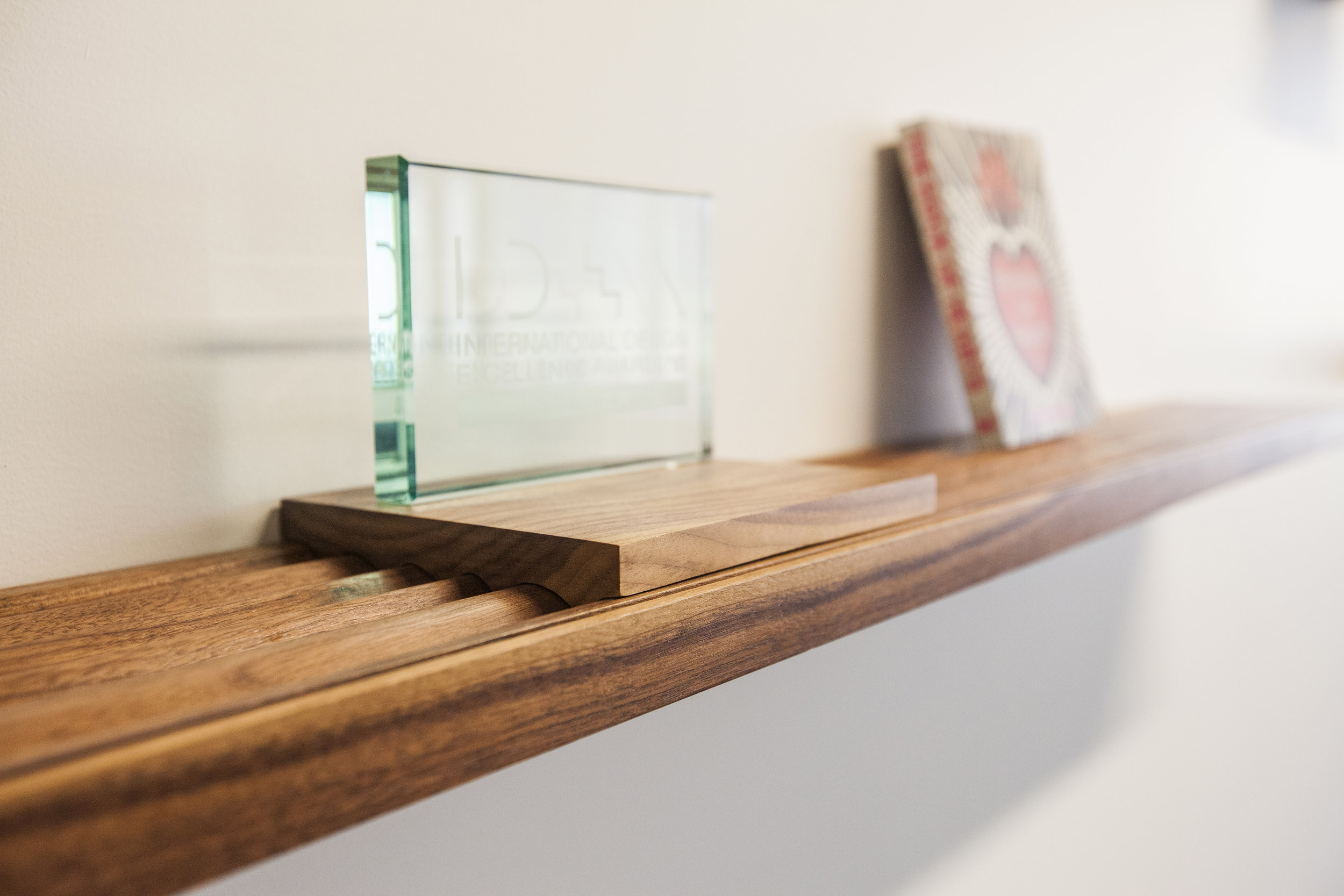 The grooves in the shelves allow for leaning different sizes of books, magazines and other printed materials. These small blocks carved with the same relief pattern sit on top the grooves and allow for awards and other items that need a flat surface.
