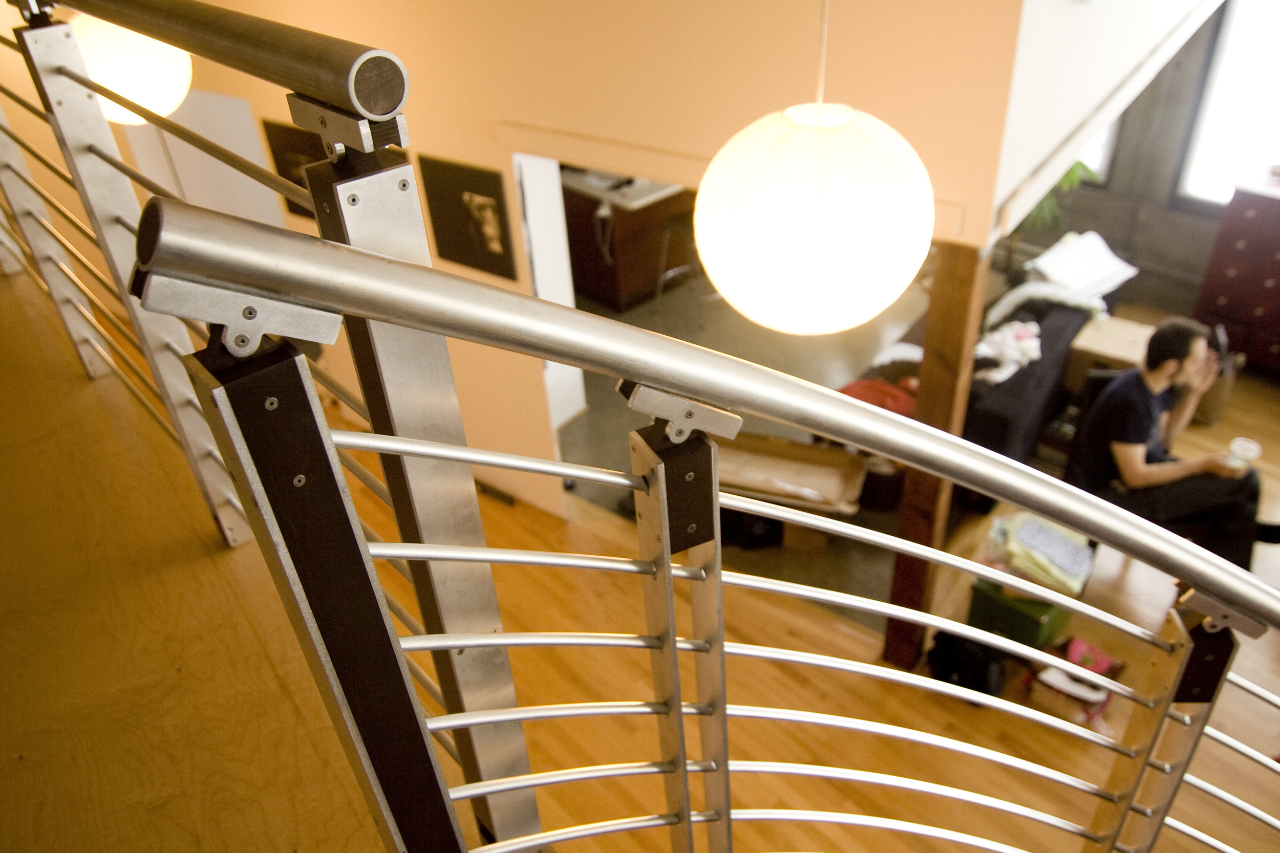 The playful almost-intersecting railings at the top of the stairs add a fun interest.