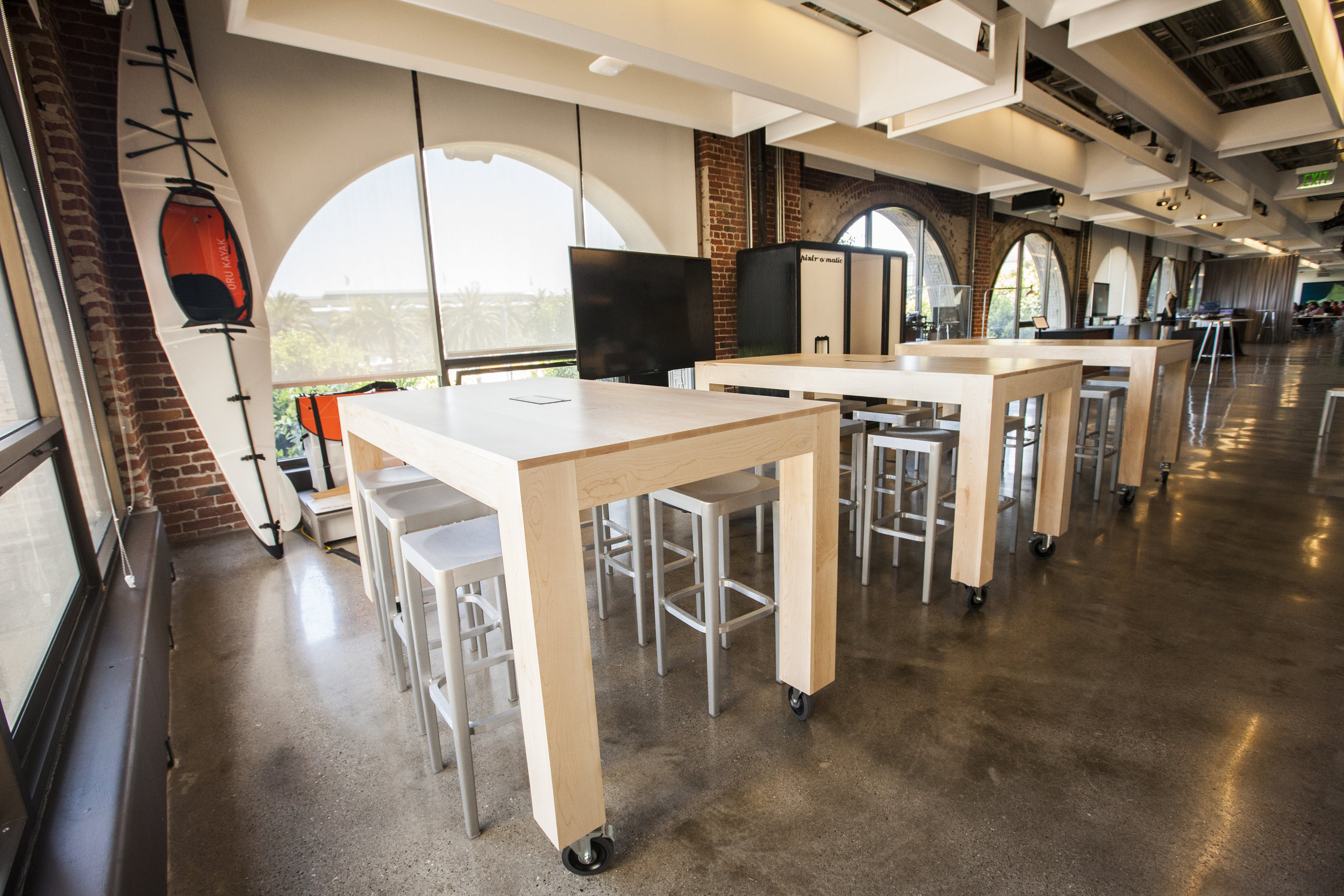 Large maple hardwood tables, made to be durable and highly functional for gallery classes and presentations. These tables at The Autodesk Gallery in San Francisco are standing height, have locking caster wheels and center power units.