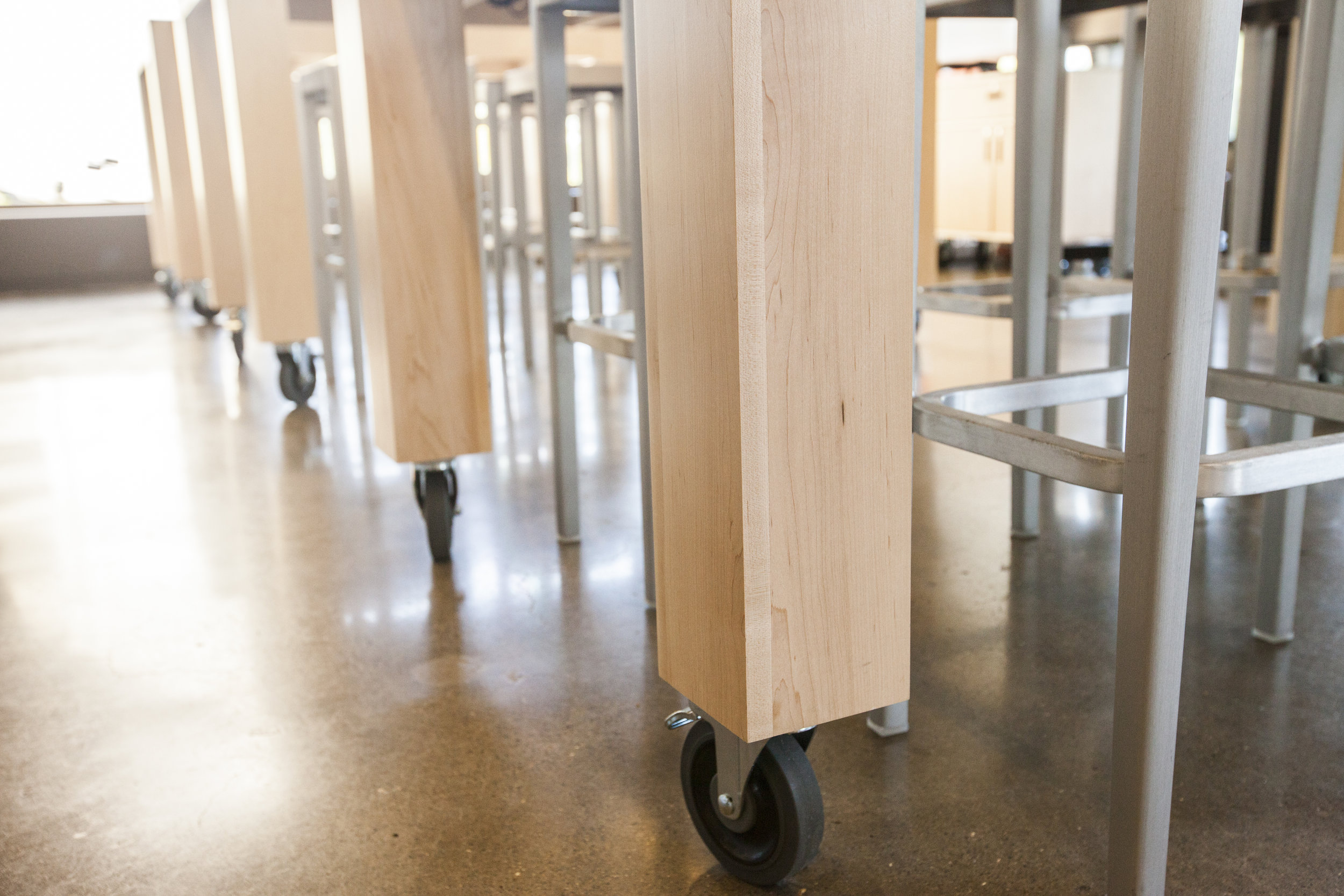 Sharp square legs end in large non marking casters.