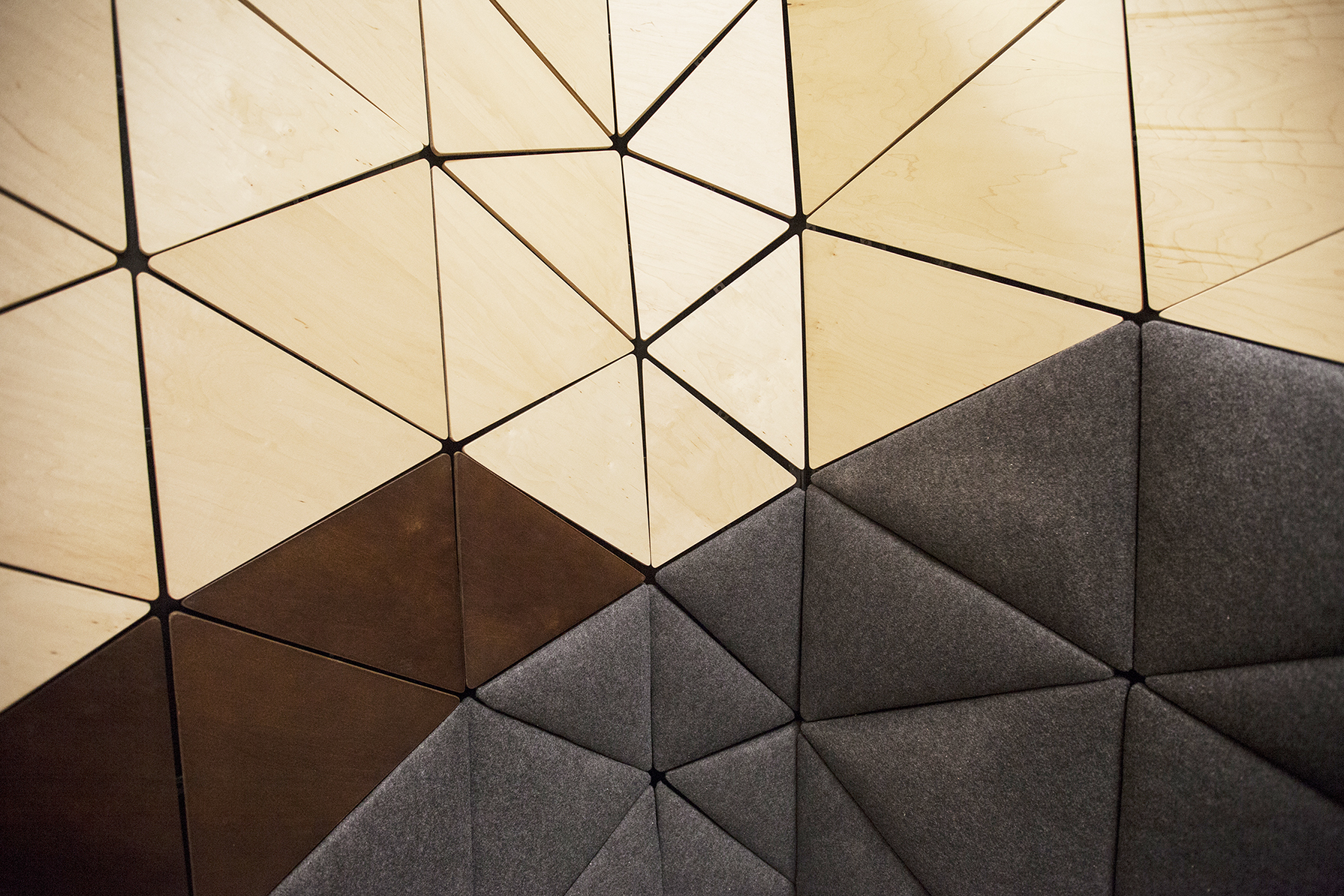One container, an undulating wall form made of triangles. Dark and padded on the bottom, bright and warm on the top.