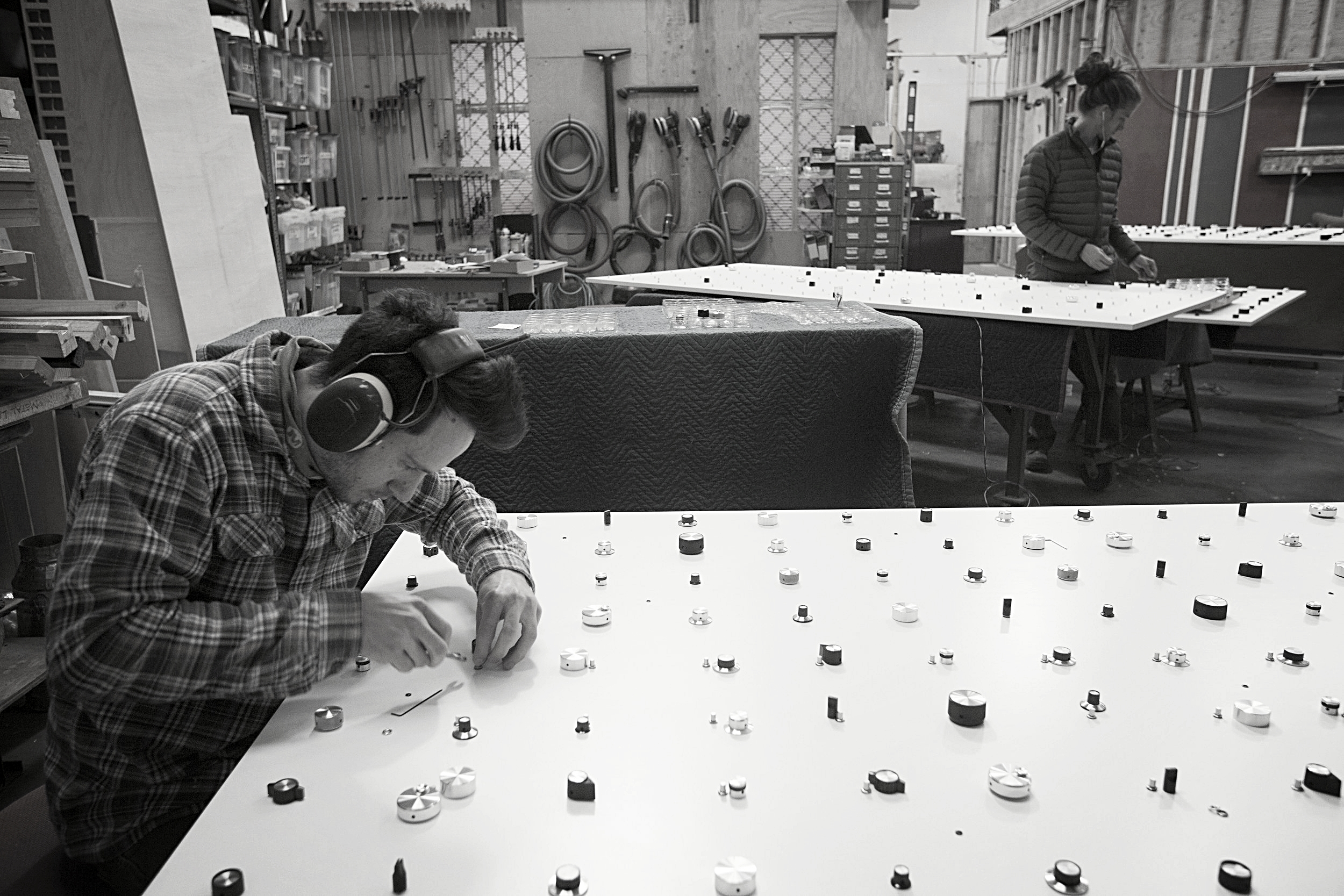 In our fabrication shop,one by one, Joel attaches the 1287 knobs across the ten 8ft tall panels.
