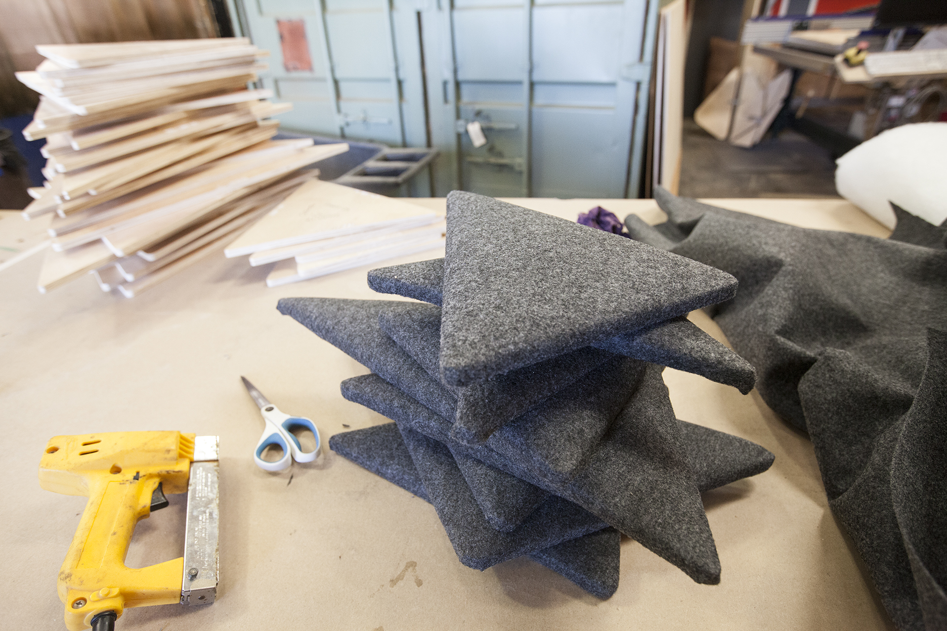 A pile of soft grey felt panels ready for client approval.