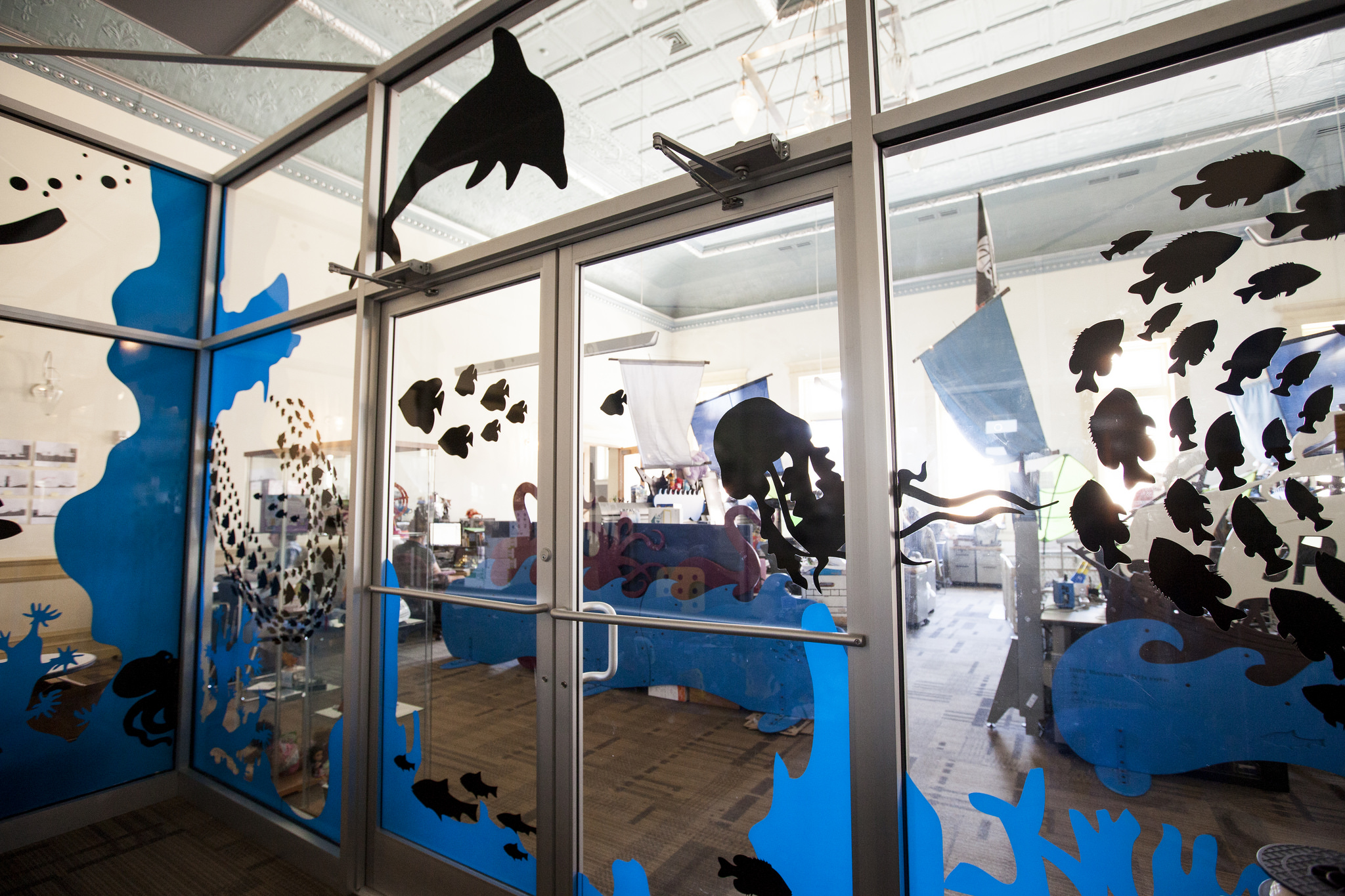 In the center of the open office stands a meeting room with all glass walls that was referred to as 'the fish tank'. We playfully covered it with an under water theme of fish, coral and divers. The vinyl application adds a need privacy to the meeting room.