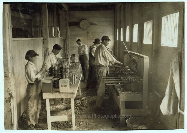 """Al interior del taller de la Sanitary Ice Cream Cone Co. Los niños que empacan los barquillos son John Myers, 14 años, y un chico de 12 años que ya trabaja de planta. Su jefe dijo: """"Me dijo que no iba a la escuela, por eso lo acepté."""" Oklahoma City, Oklahoma, abril 3, 1917."""