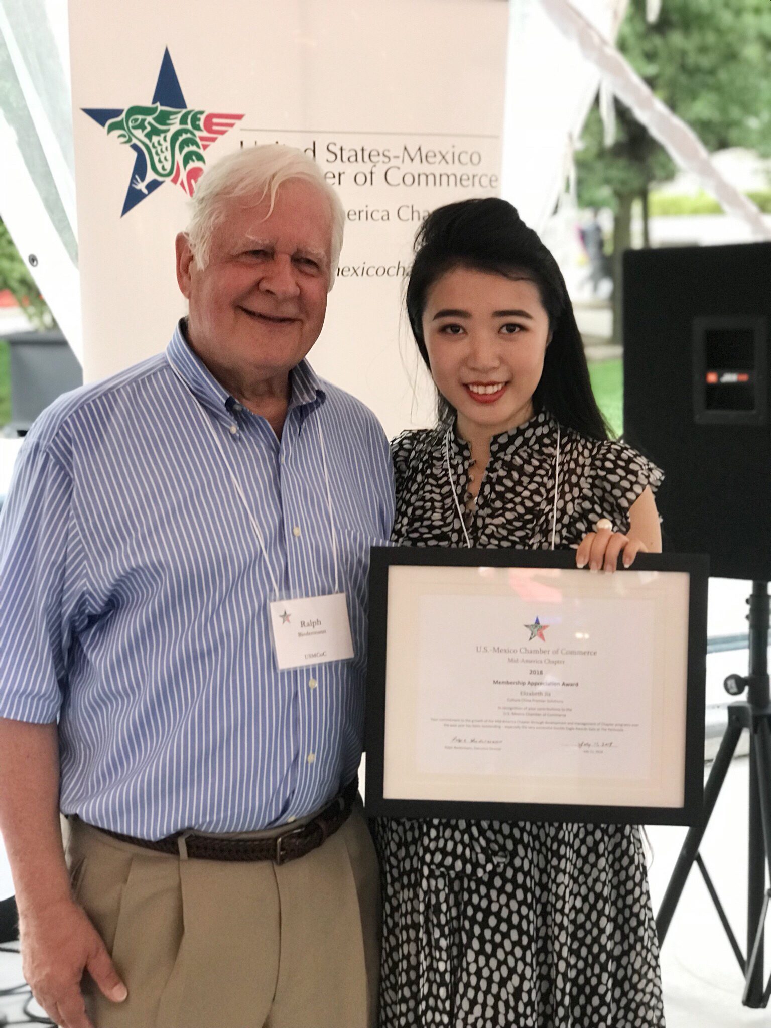 Executive Director Ralph Biedermann presenting a recognition award to Elizabeth Jia, who manages programs and development for the Chamber