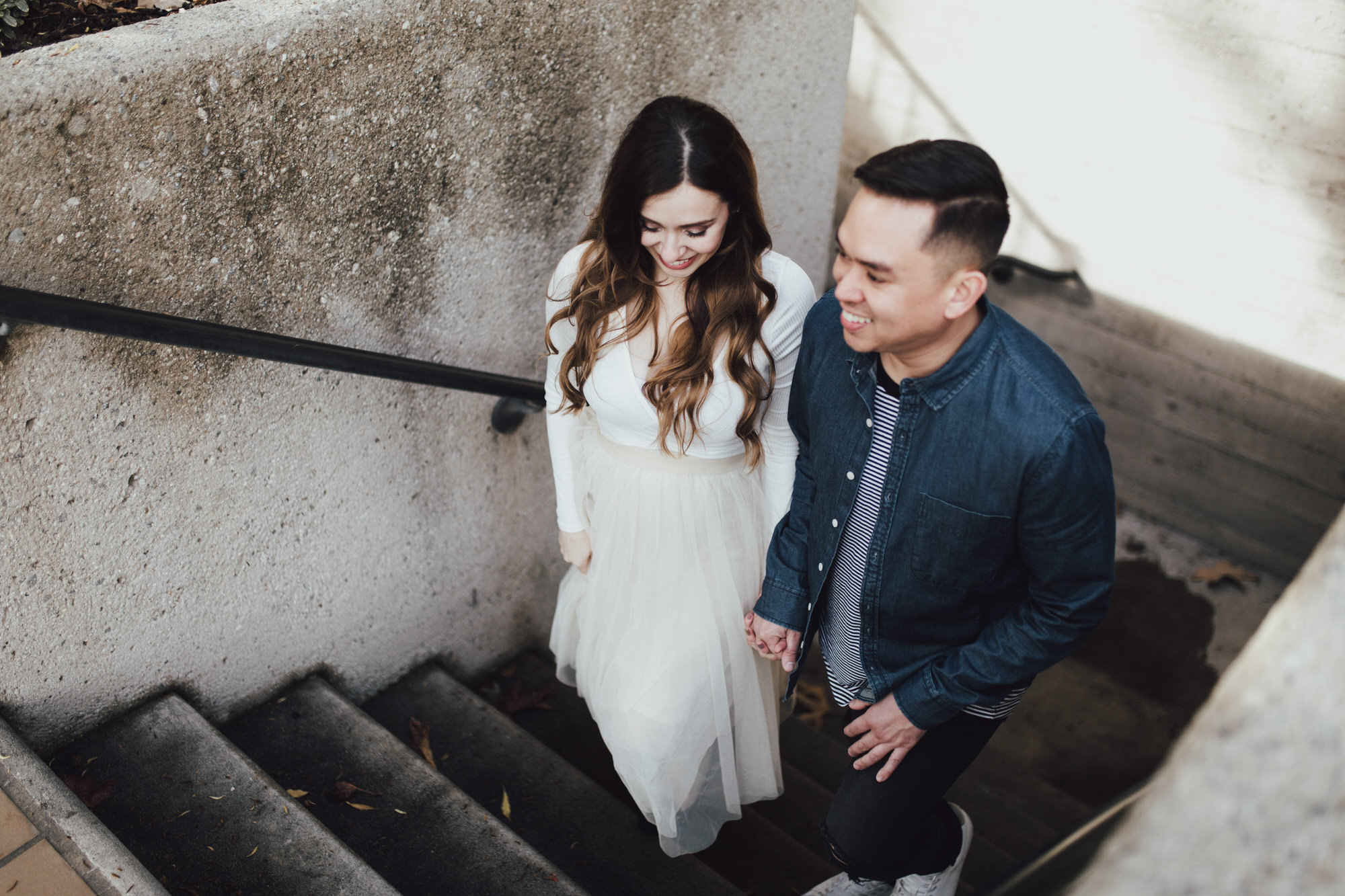 candid engagement photos on staircase by pomona university