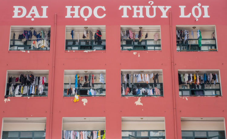 Laundry hangs to dry in the windows of a red apartment building in Ho Chi Minh city.