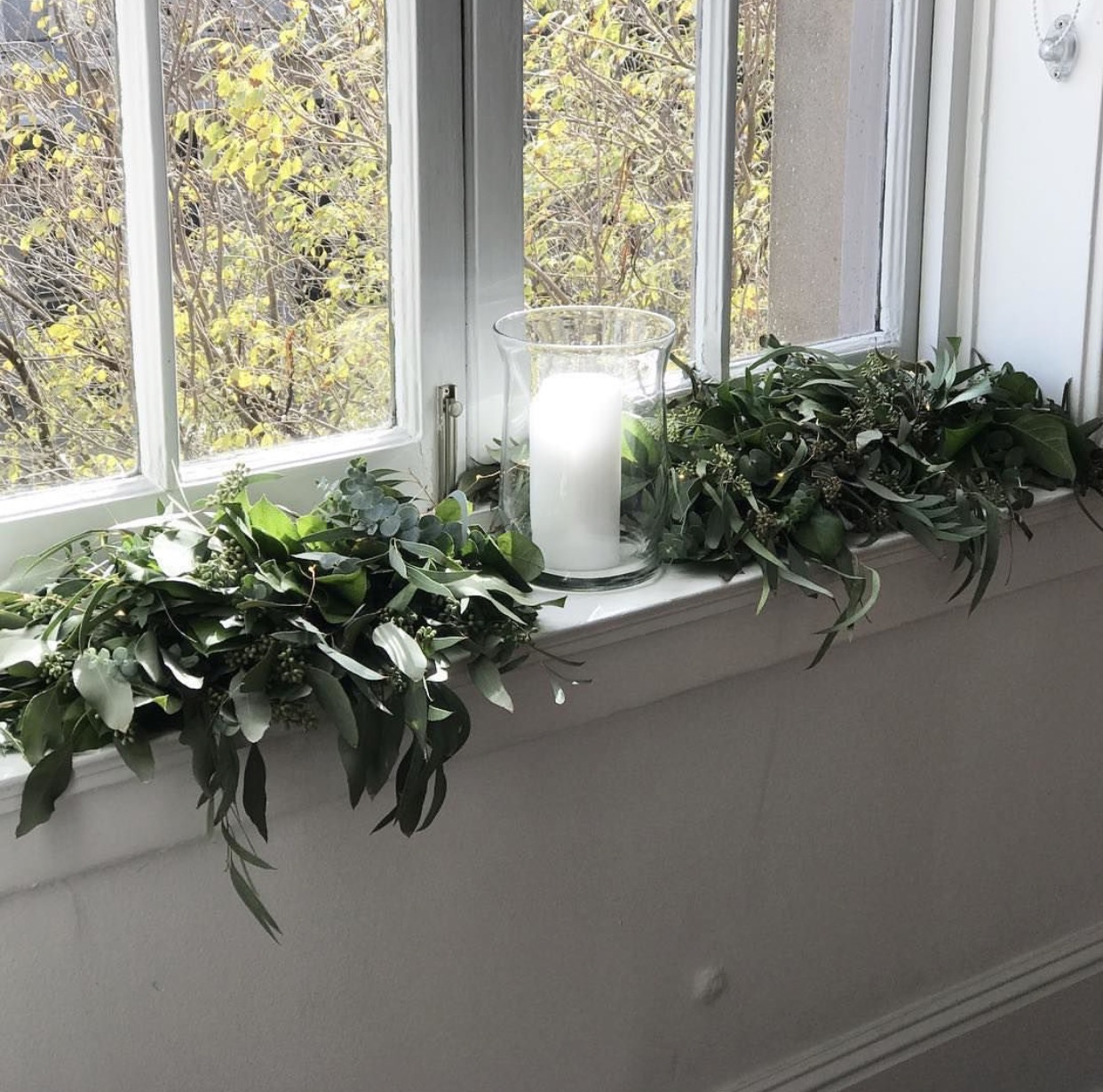 lush winter garlands in the window #Lrqcfloral #floralgarlands