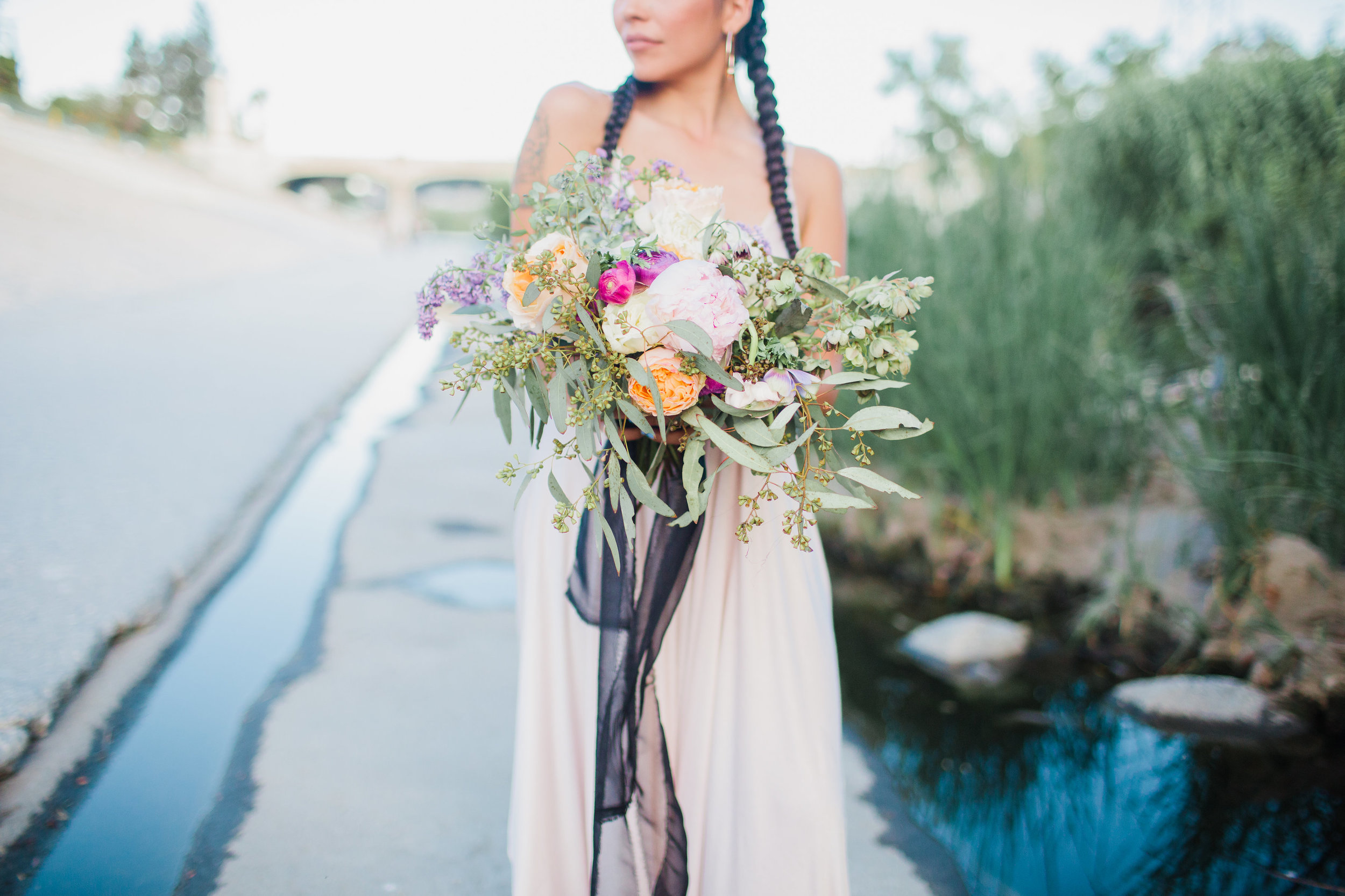latina bride at the la river with purple bouquet #lrqcfloral #gaywedding