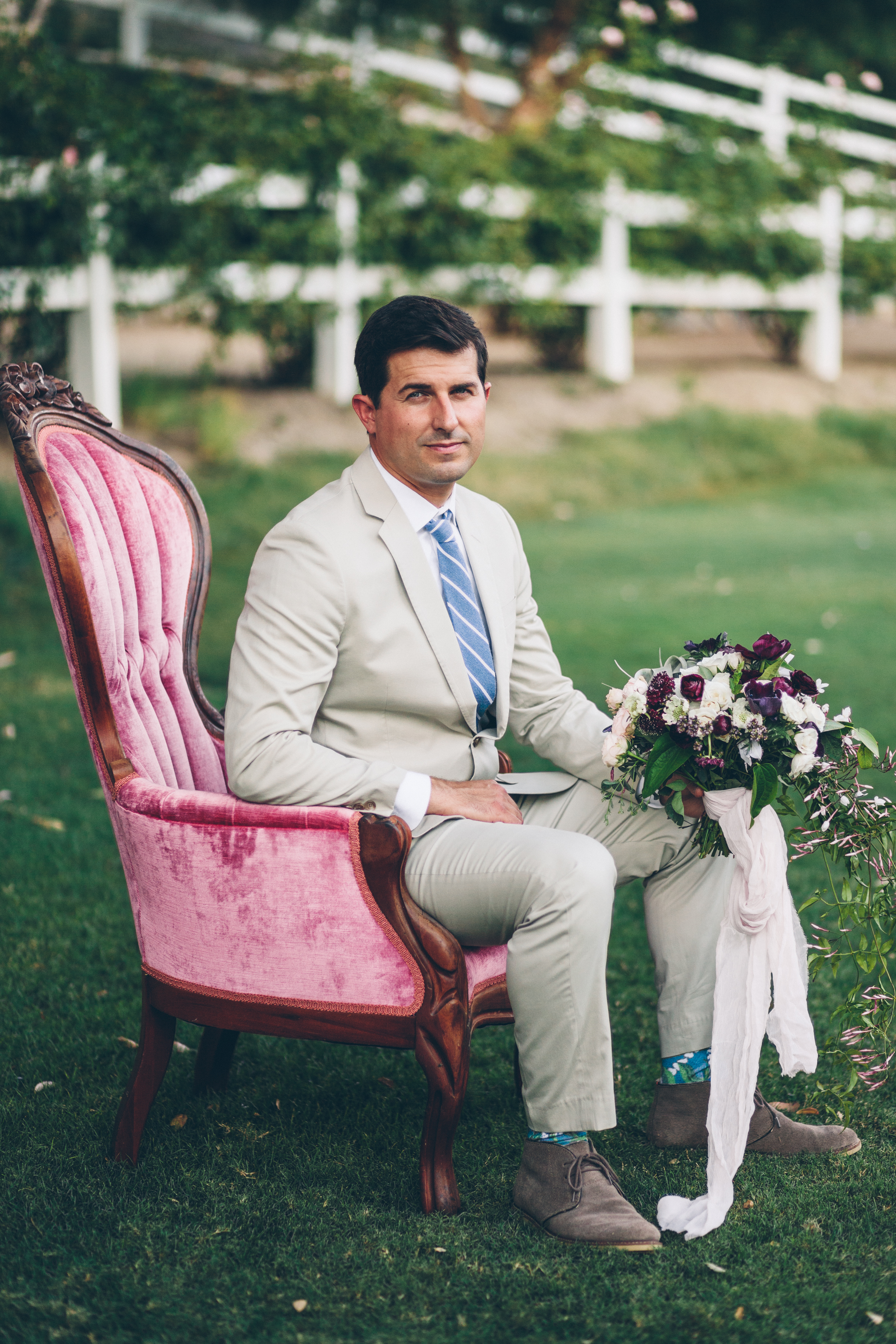 groom in beige tux holding a purple and blush airplant bouquet.jpg