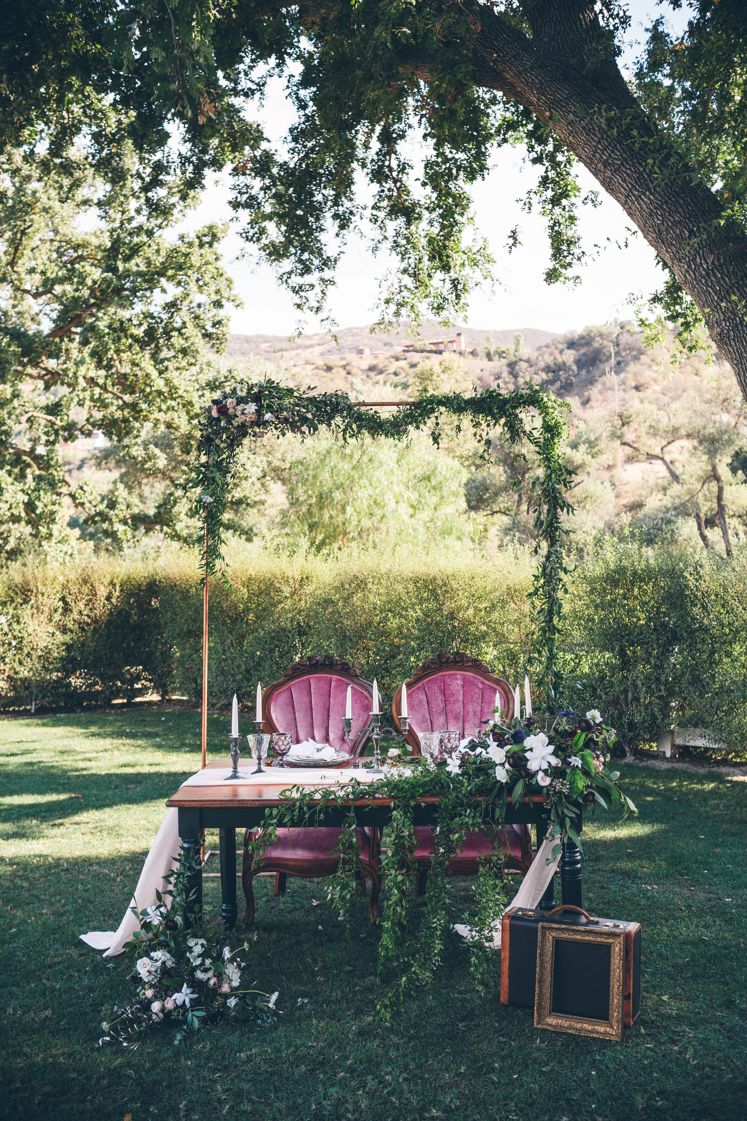 sweetheart table with flowing flowers and a copper arch .jpg