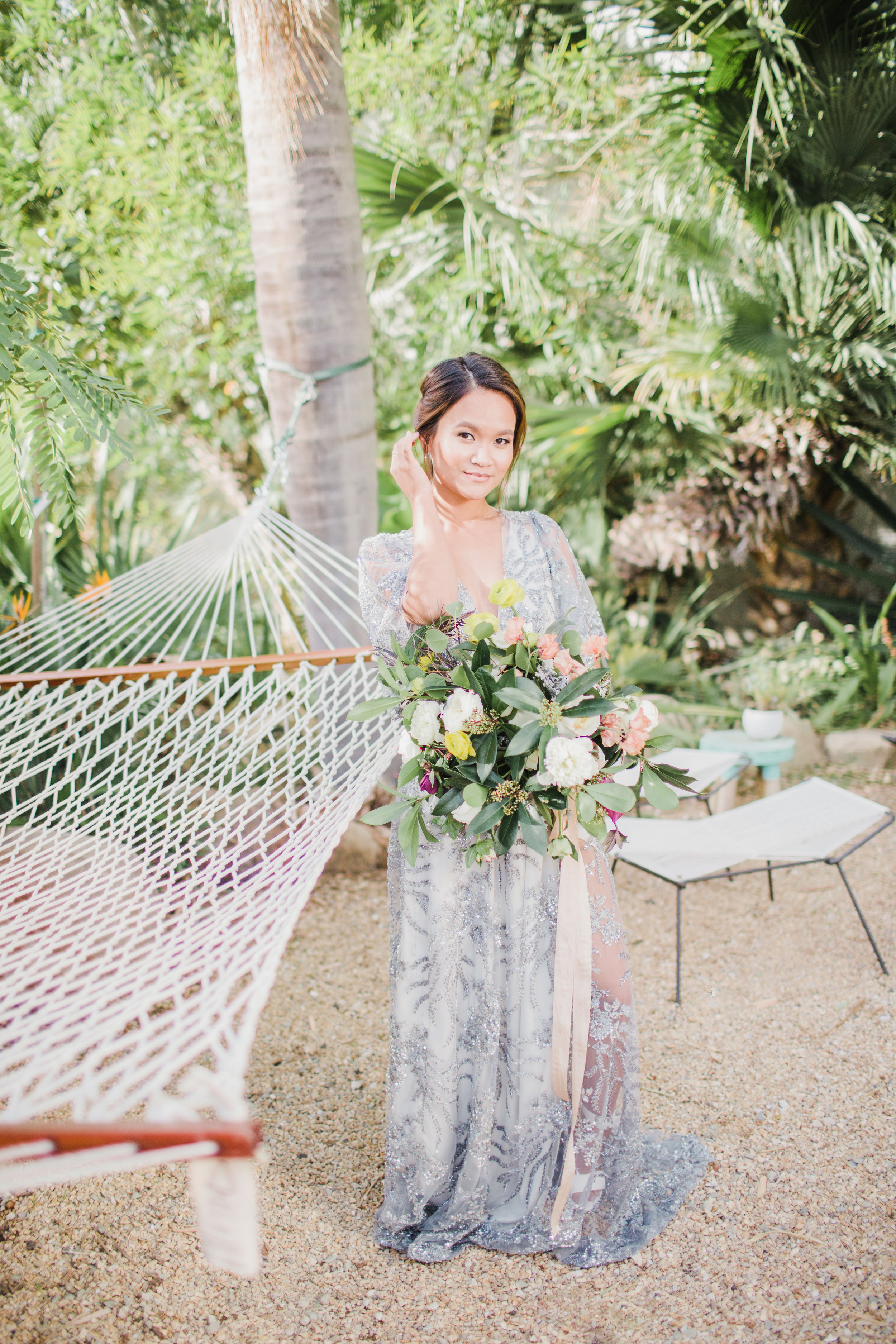 Grey wedding dress in Santa Barbara with big bouquet with purple and yellow flowers.jpg