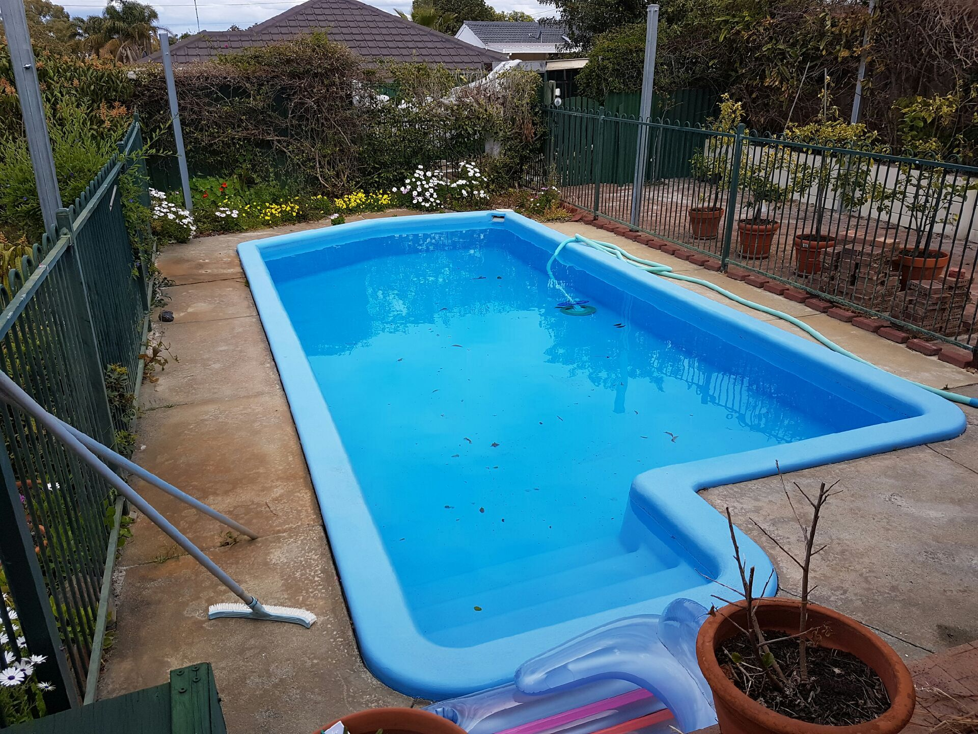 Before:  This outdated pool area needed some work, with new paving and fencing.