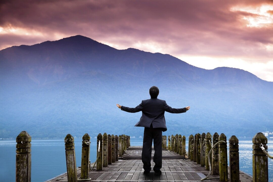man in suit on jetty with mountain.jpg