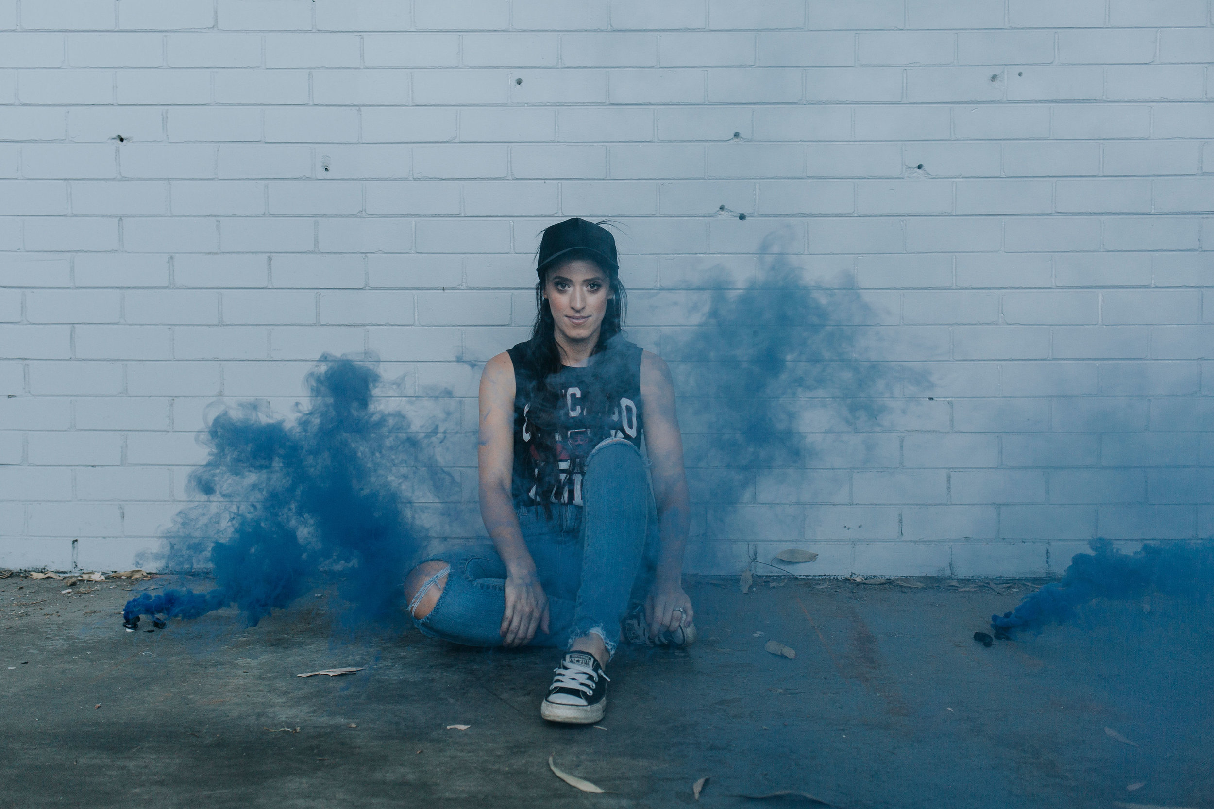 Girl with blue smoke bomb in abandoned warehouse