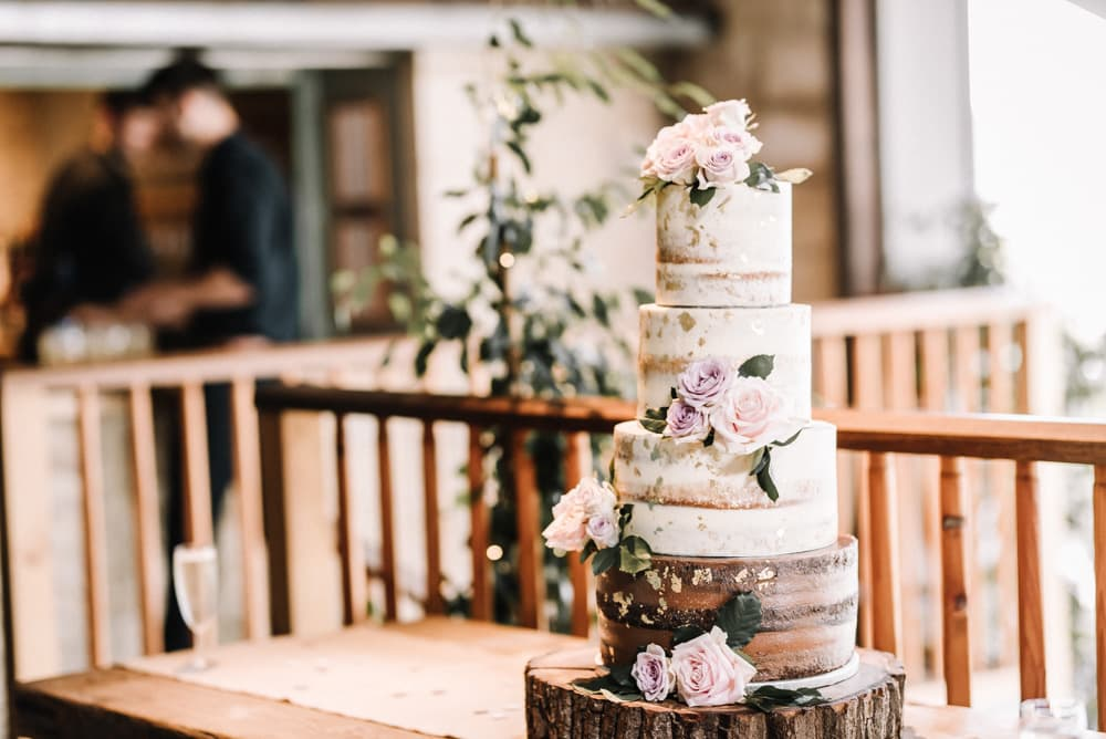 semi naked wedding cake with gold leaf and roses.jpg
