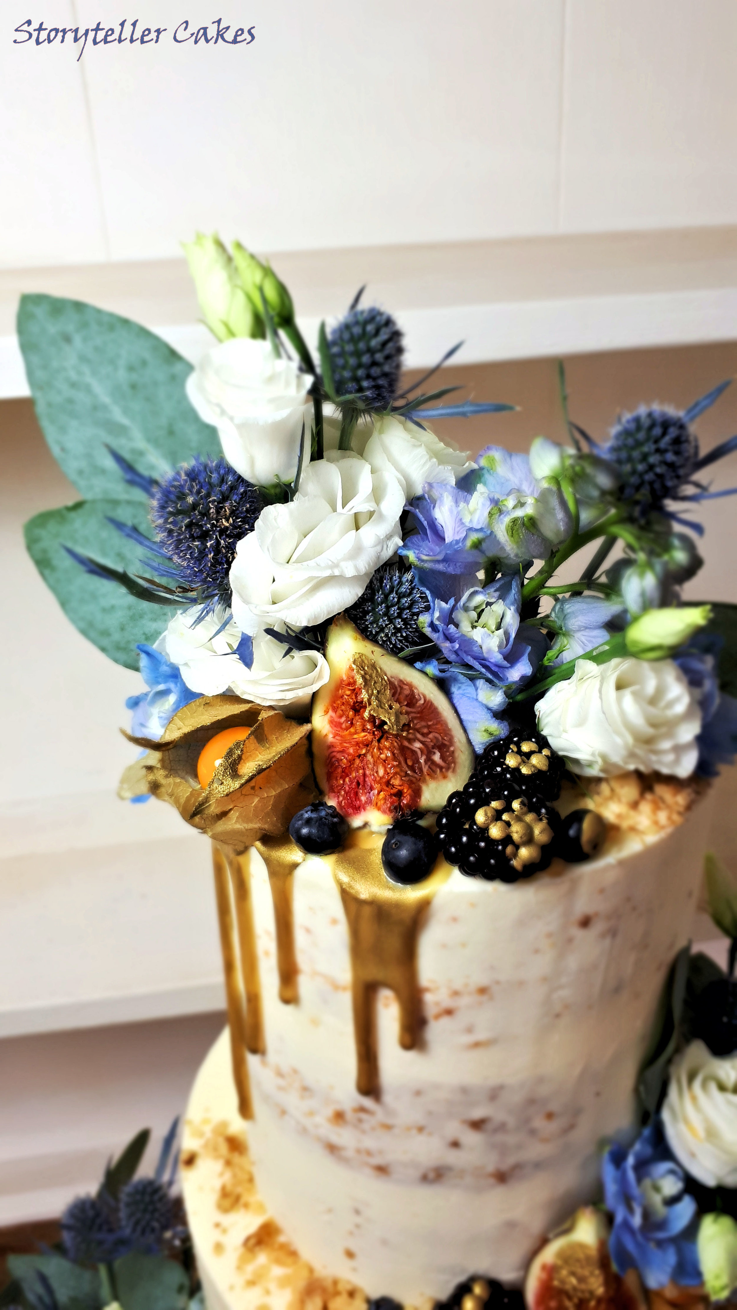 Semi Naked Wedding Cake with Blue and gold thisltes and fruit.jpg