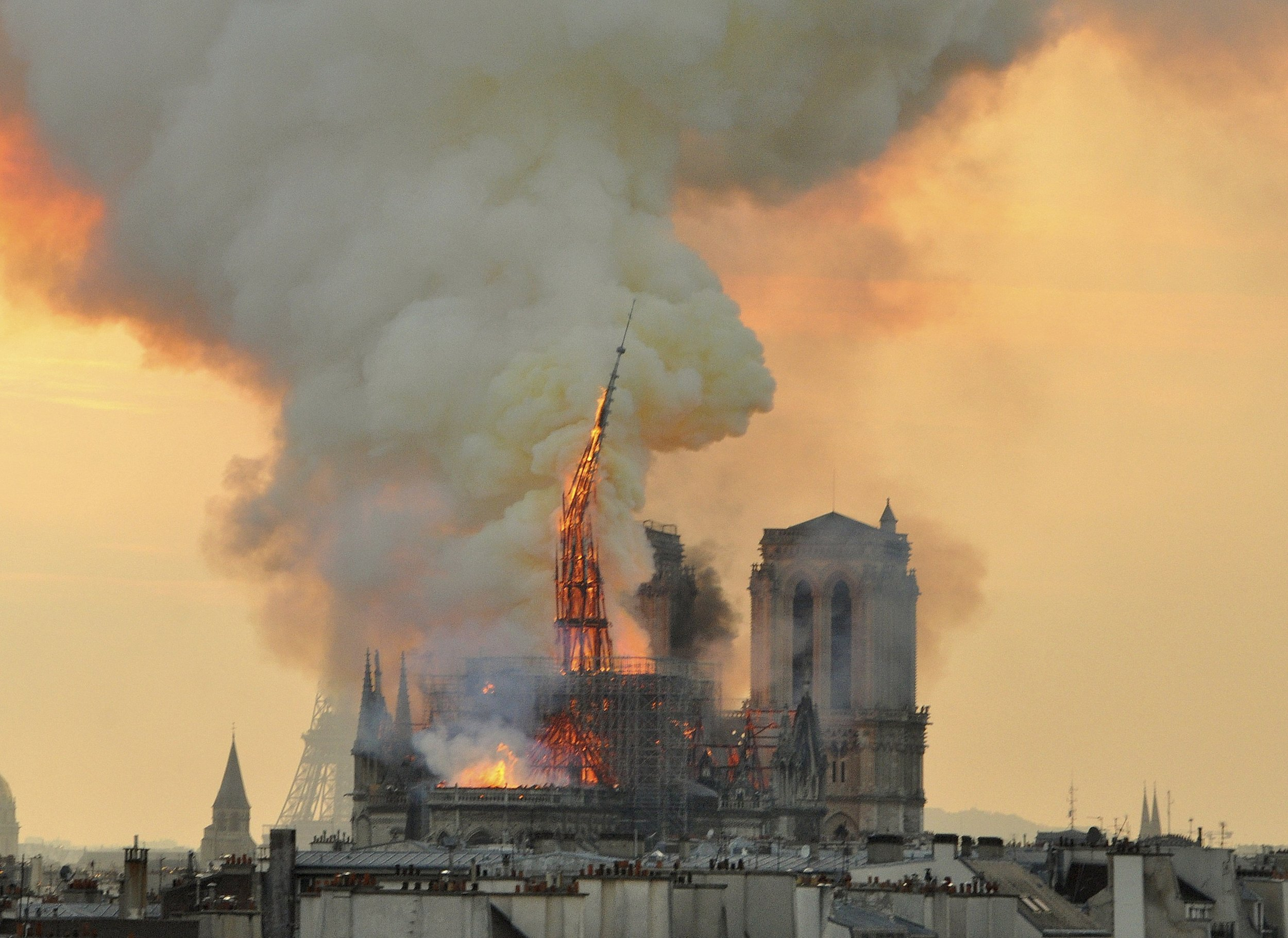 Flames and smoke rising from the blaze as the spire starts to topple on Notre Dame cathedral in Paris, Monday, April 15, 2019. (AP Photo/Thierry Mallet)