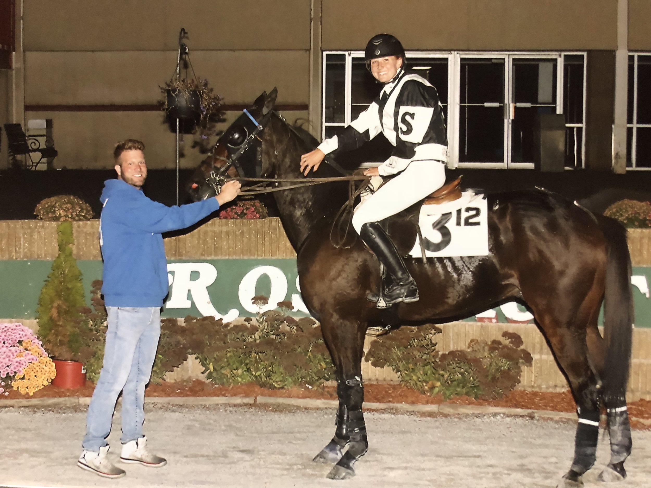 Egosnattitudes, ridden by Sofia Zingale in the Rosecroft Winners Circle along with Joe Colombo (left). Photo courtesy of Ed Cioffioni of Best Bet Photos.