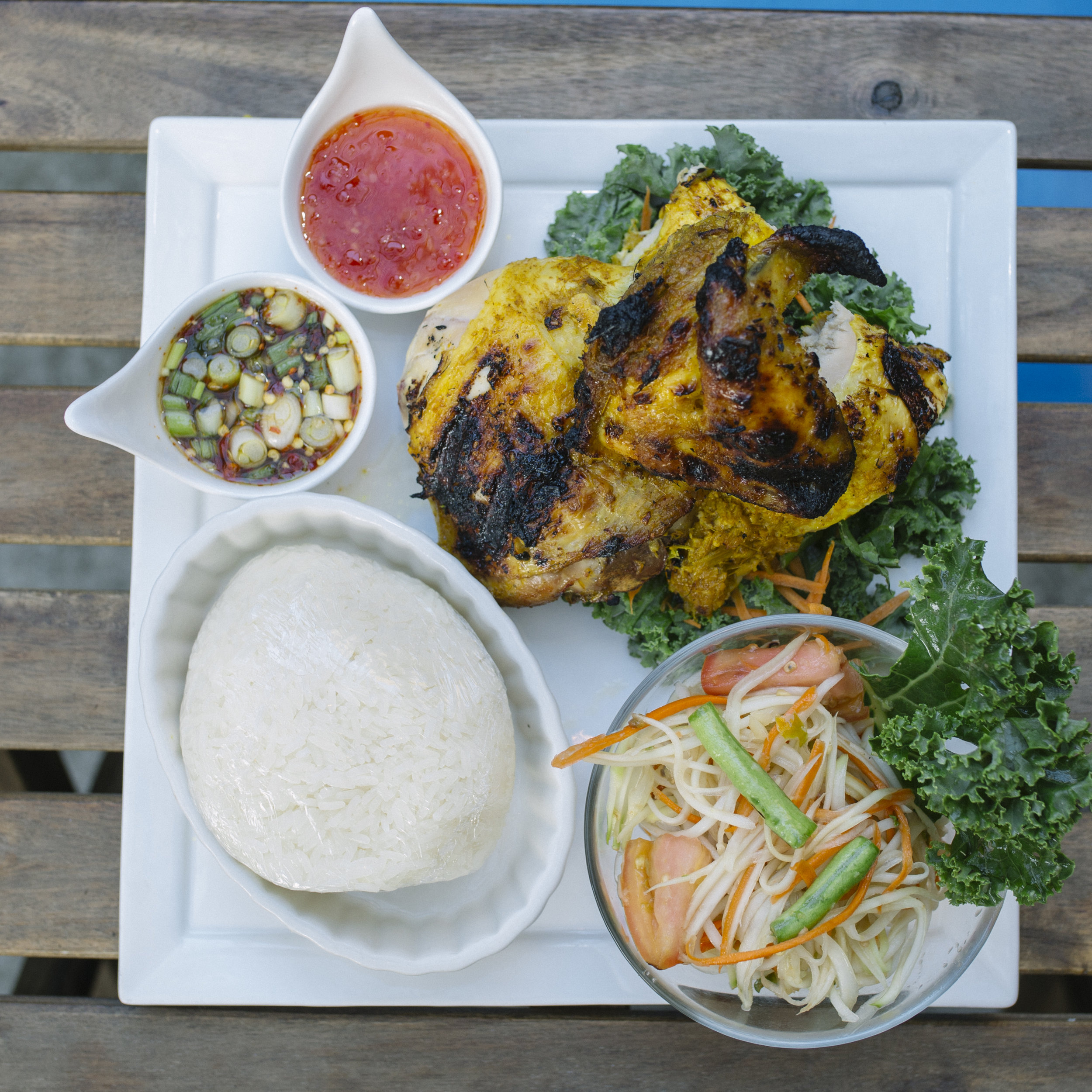 Gai Yang Khao San Kwang - Half Chicken Marinated with Herbs and Roasted to Perfection served with Tum Thai and Sticky Rice