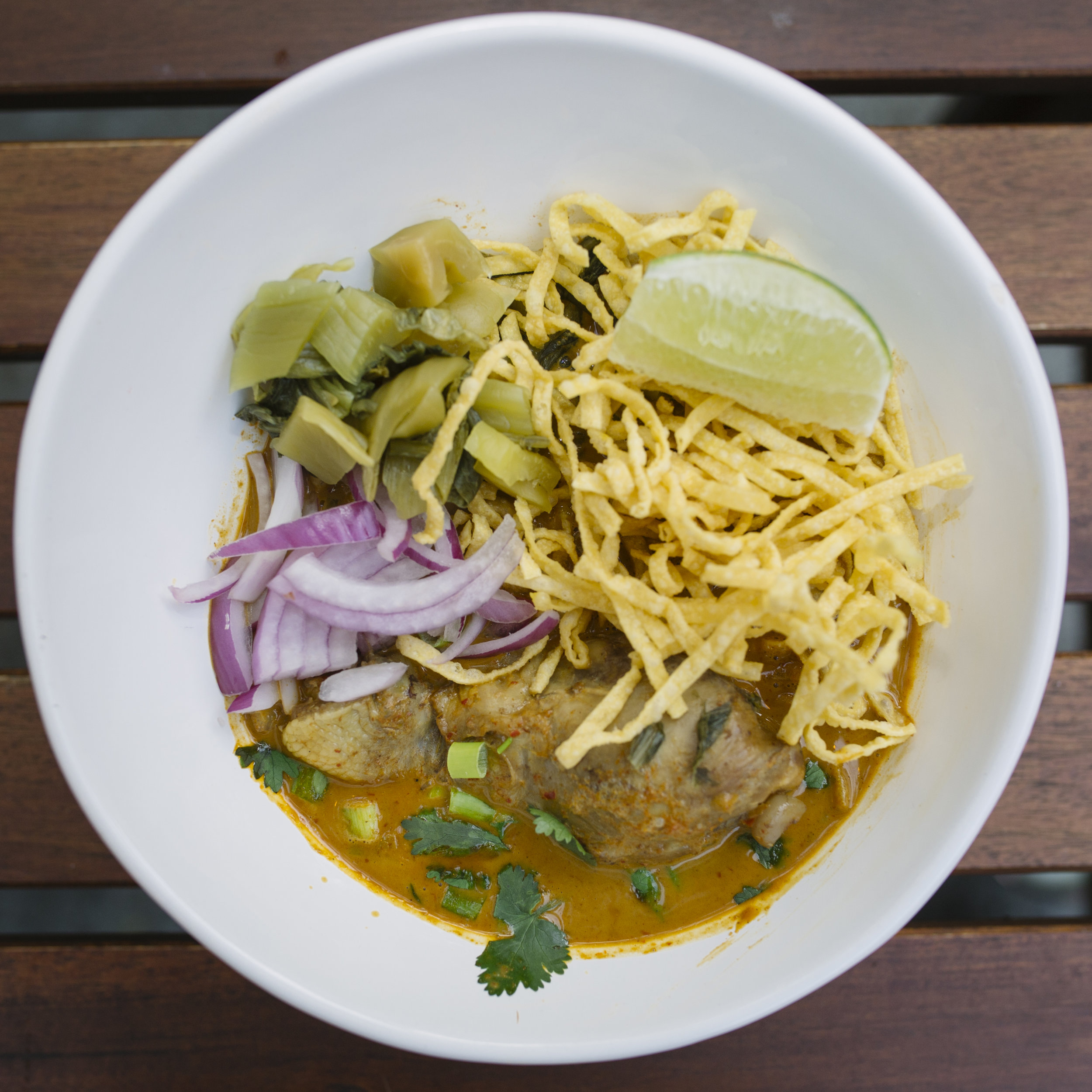 Kao Soi - Egg noodles with chicken or vegetables simmered in curry soup, topped with crispy egg noodles, pickled mustard greens, red onions, lime, and chili oil