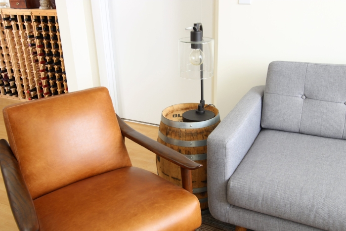 This table is an old whiskey barrel that the client got from a local distiller. They were selling old ones, and he snapped up two to use for tables. They are a great addition next to the leather chair from West Elm and gray sectional from Gilt.