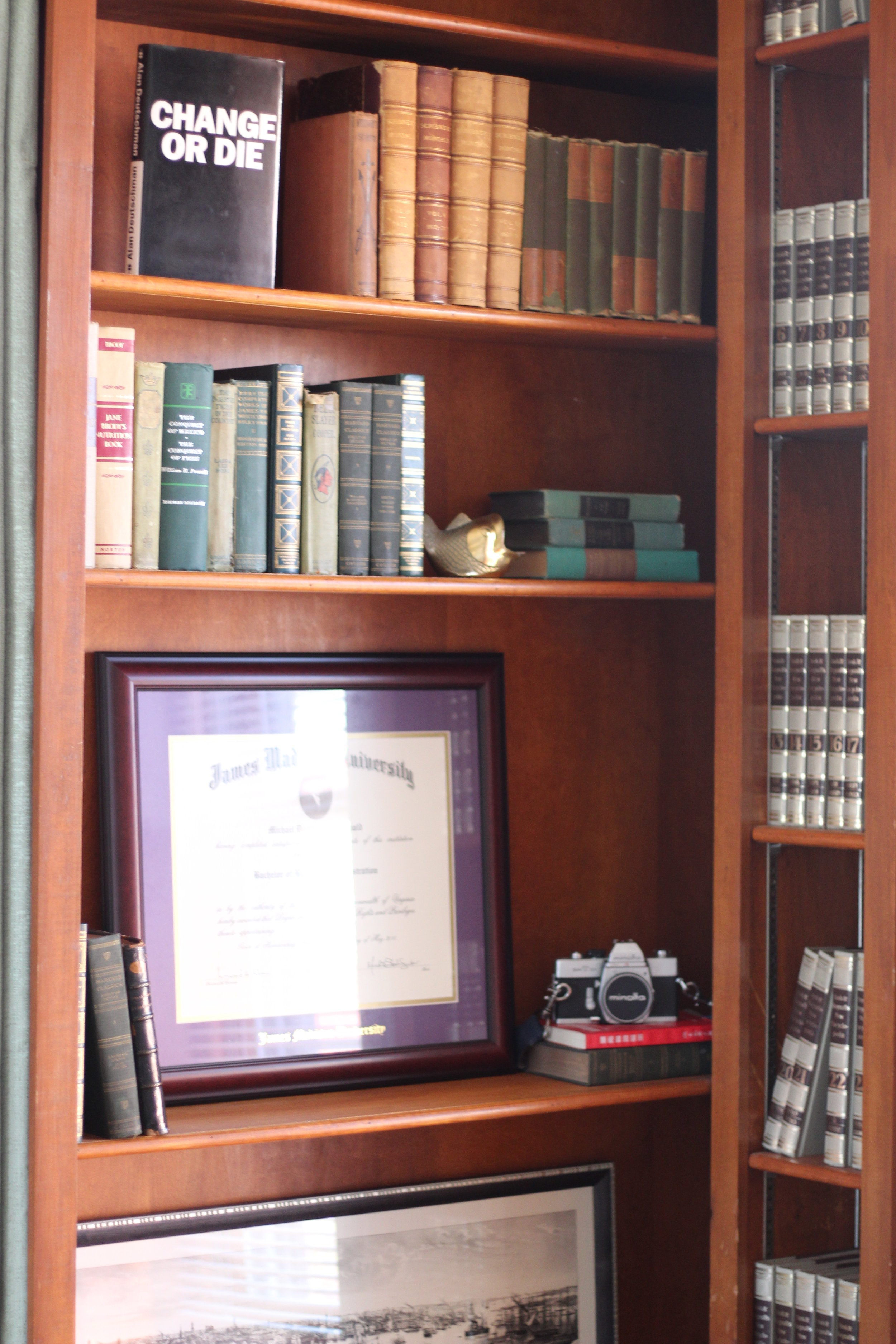 A close up view of the workspace, this corner houses the client's diploma, a sometimes too true feeling book cover and an old encyclopedia set.