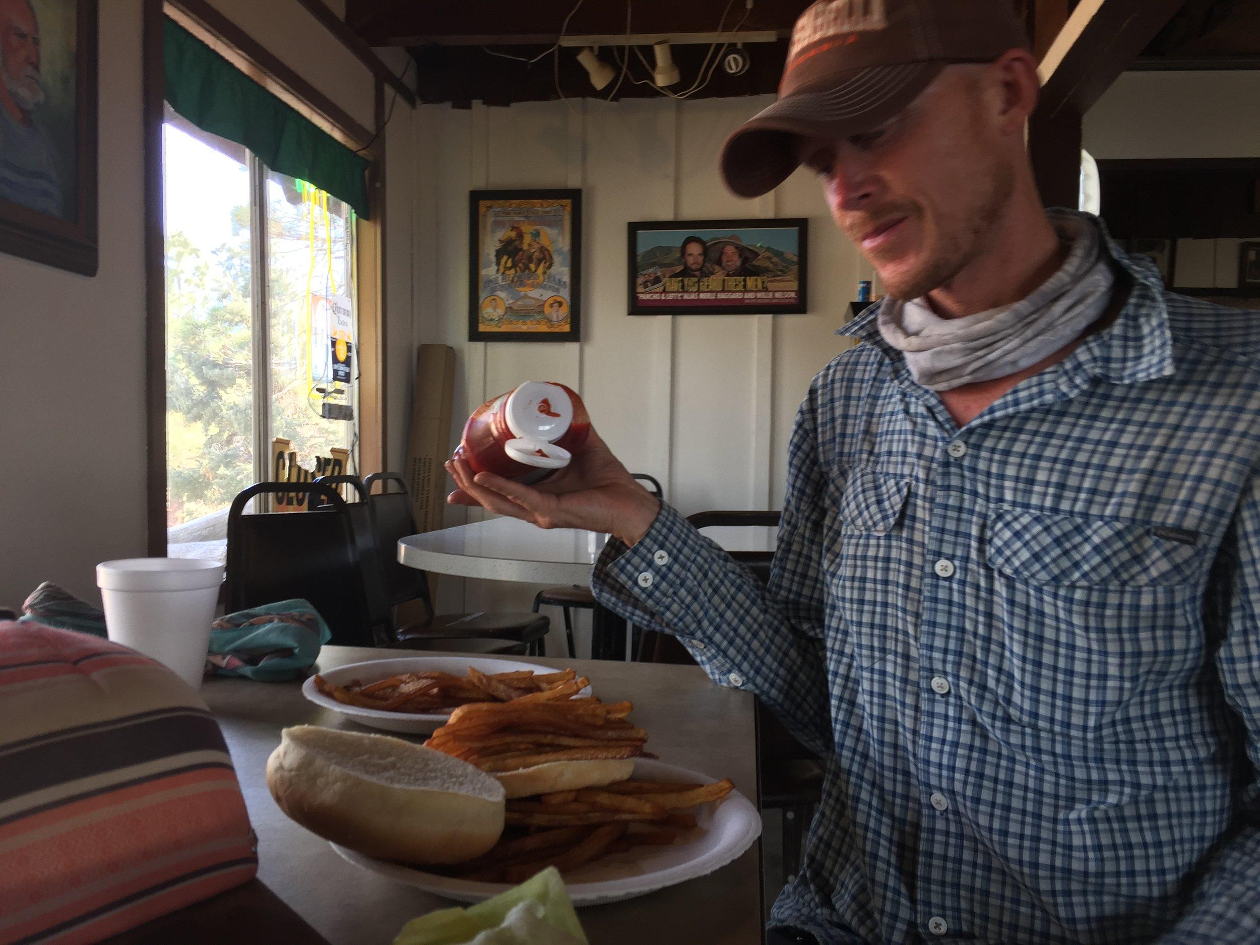 "Utah Aaron adding ketchup to his French fry ""burger"""