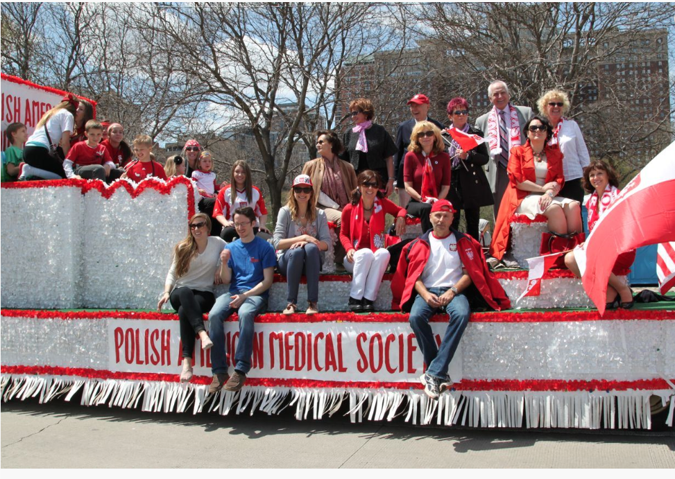 Members and families of the Polish American Medical Society enjoy the beautiful weather on their patriotic May 3rd Parade float.