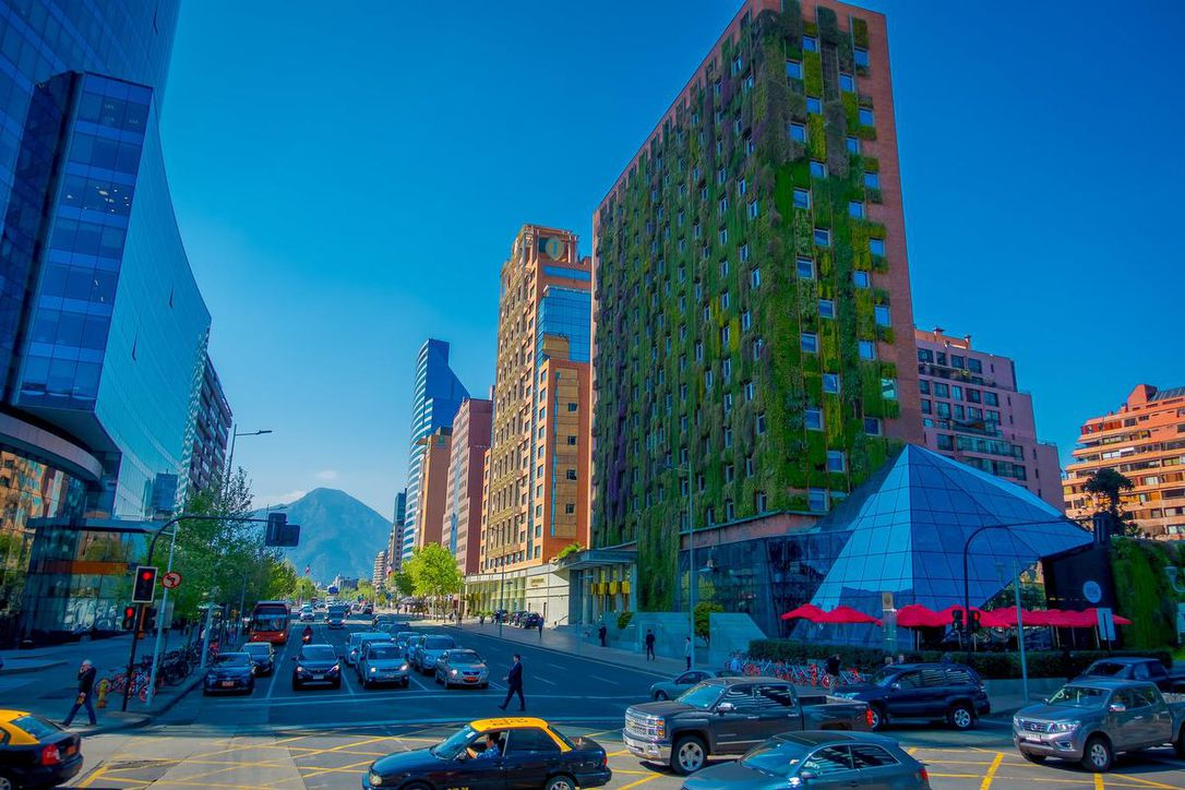Outdoor view of green building in Santiago de Chile with modern office buildings at financial district in Las Condes. Architects have seen buildings as a possible solution to the climate crisis, but it needs policy, regulation and incentives in order for it to become business as usual, write Meg Holden and Rebecca Holt. (PABLO HIDALGO / DREAMSTIME)