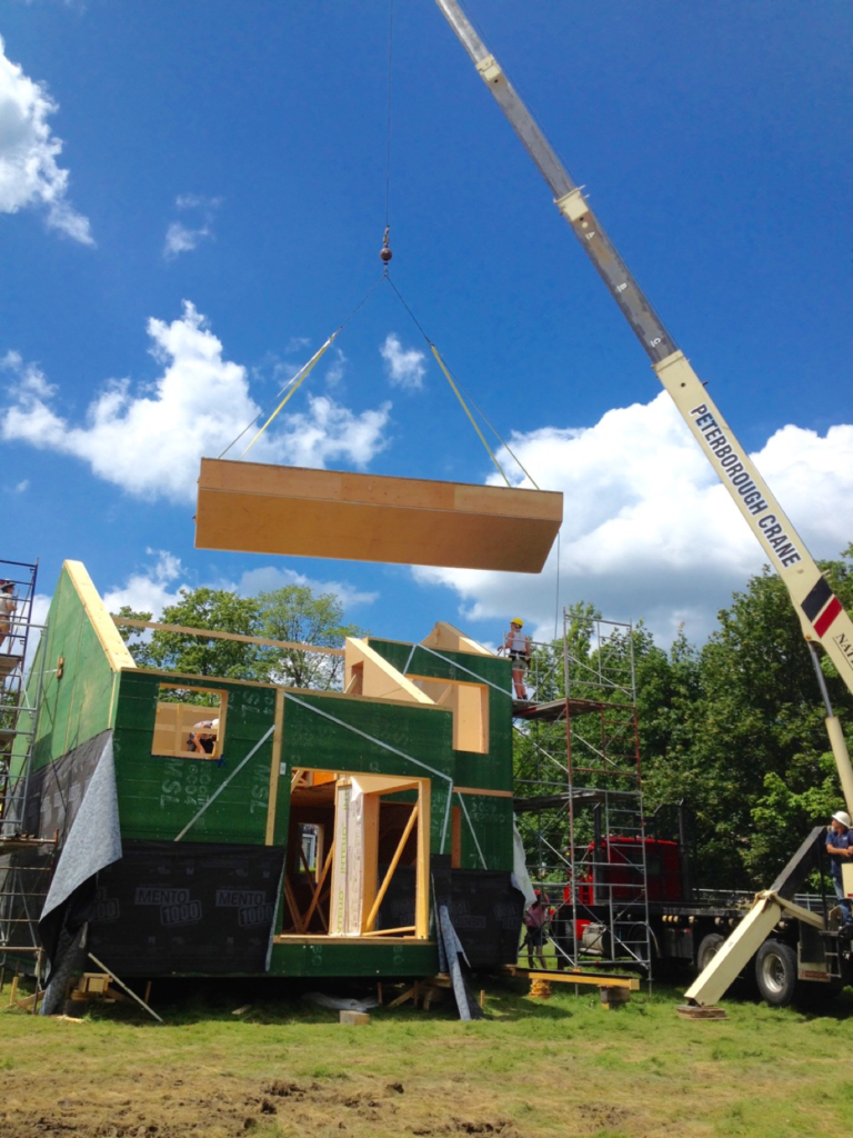 A prefabricated roof section is craned on to ZEROHouse.