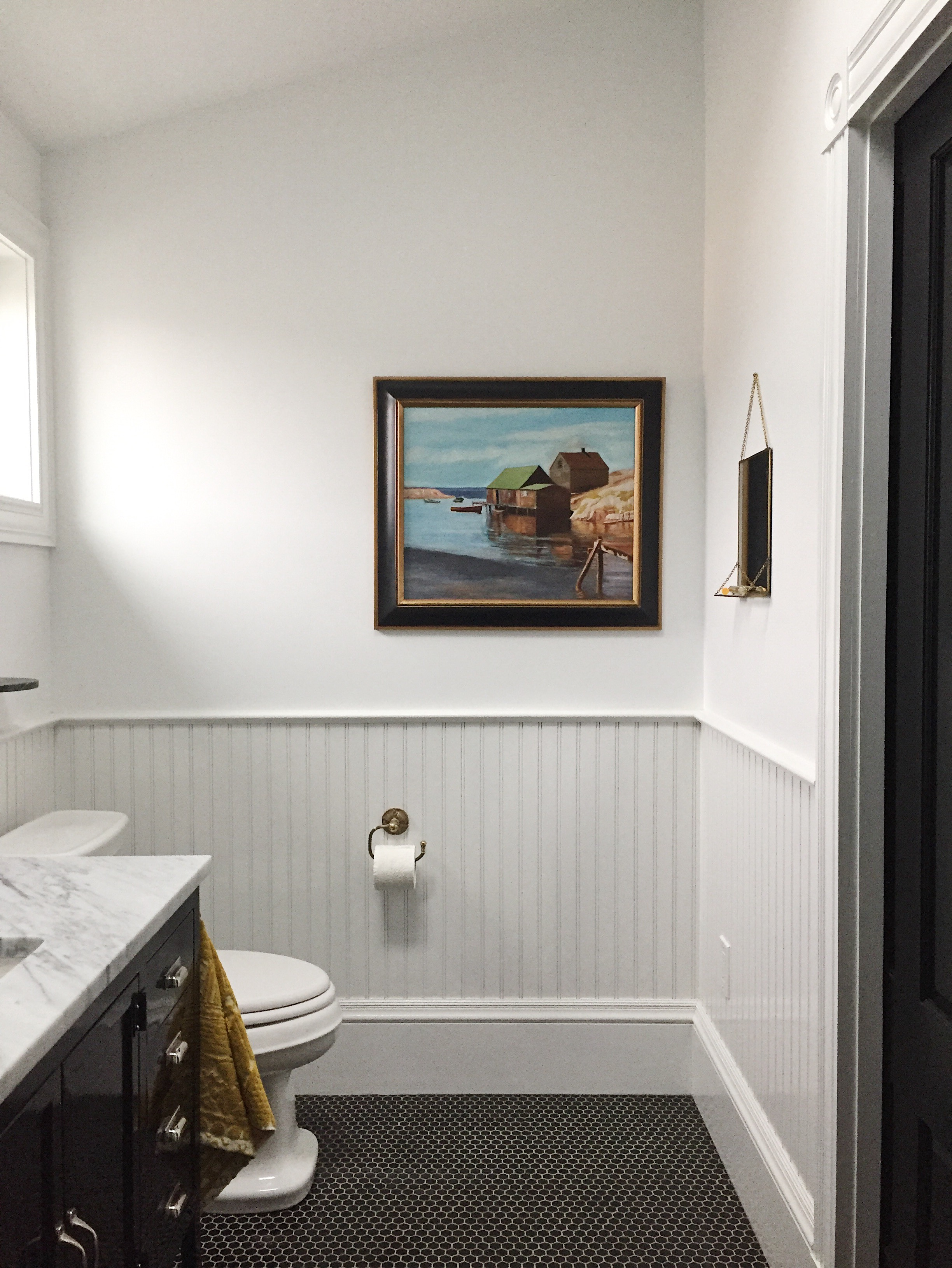 We added a bathroom (life changer!) We used a traditional glossy, black hex tile floor, wood wainscot + white subway tile in the shower.The artwork was painted by my late grandfather.