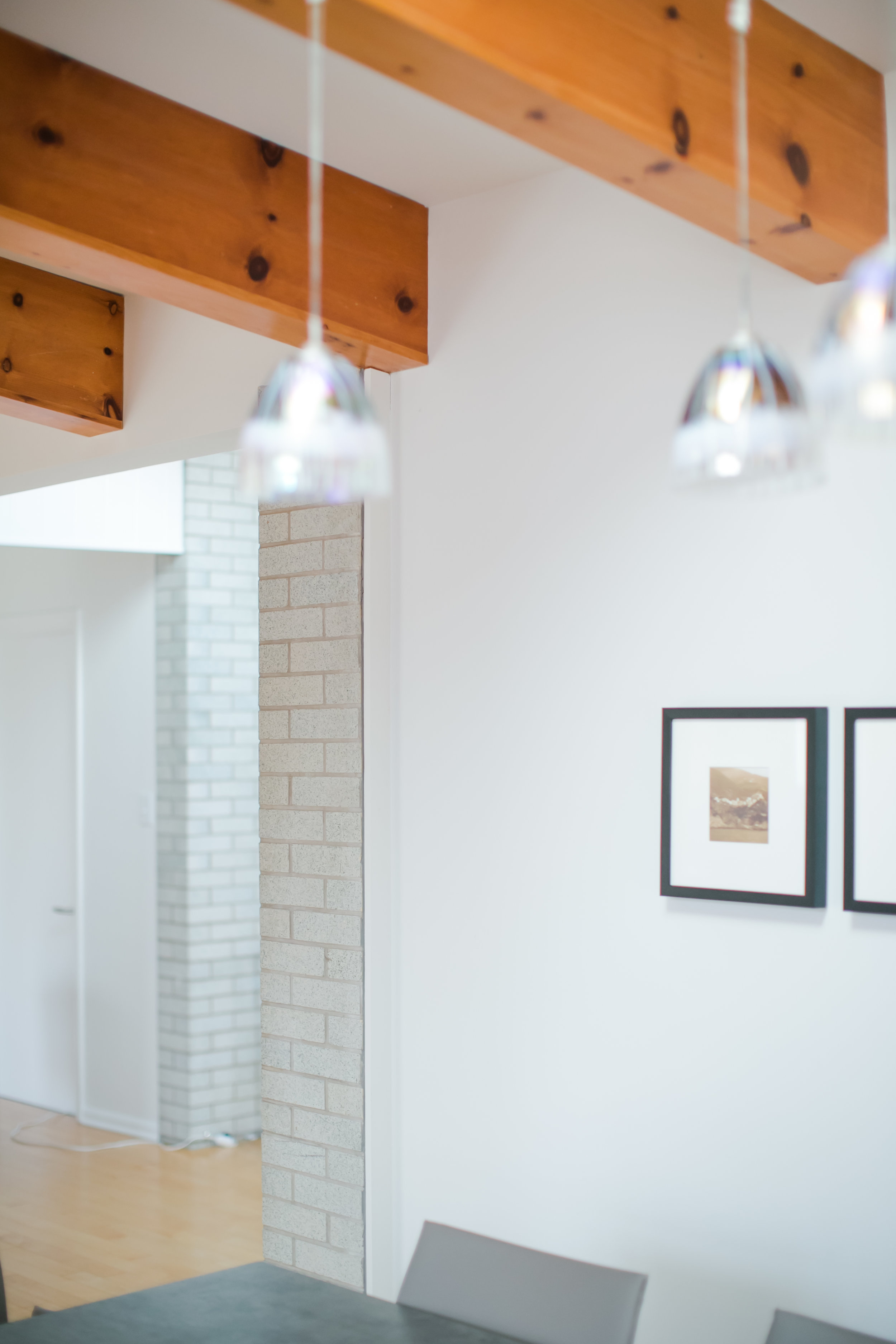 White walls, original brick, and exposed wooden beams starkly contrast the interior design of the home's new addition.