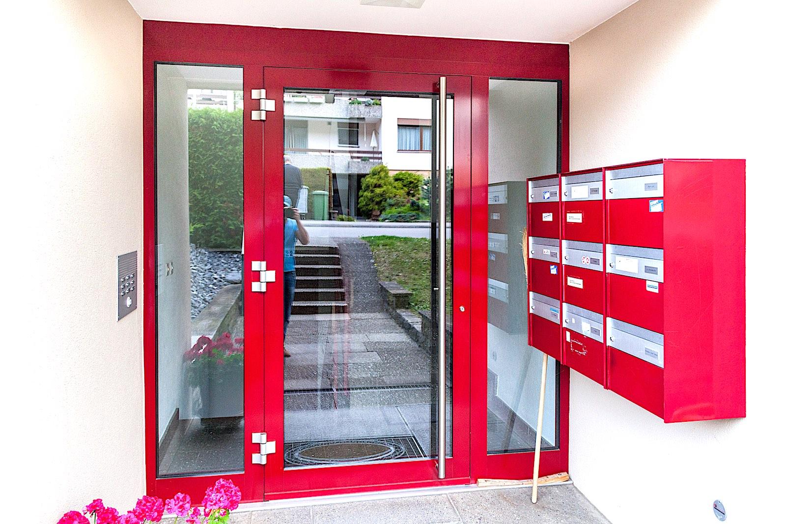 MFH in Oberweningen - Aluminium-Eingangstür nach aussen öffnend mit 2 Seitenteilen. Farblich angepasst an bestehende BriefkastenanlageVerglasung: Klarglas