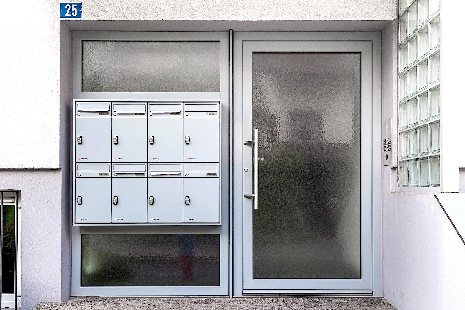 MFH in Mollis - Aluminium-Eingangstür mit Seitenteil und BriefkastenanlageBriefkasten: RENZ-Briefkasten mit Brief- und PaketkastenVerglasung: Kathedralglas
