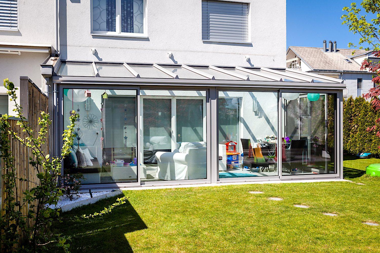 Kalt-Wintergarten in Spreitenbach - Ausführung:Aluminium-Terrassendach verglast mit IsolierglasFront:2 Stück 3-läufige Multiraum Aluminium-Schiebeverglasungen mit je einem Insektenschutz-SchiebeflügelSeite:1 Stück 3-läufige Multiraum Aluminium-Schiebeverglasung mit einem Insektenschutz-Schiebeflügel und einem festverglasten SchrägfensterVerglasung Dach und Schiebeelemente: 2-fach Isolierglas